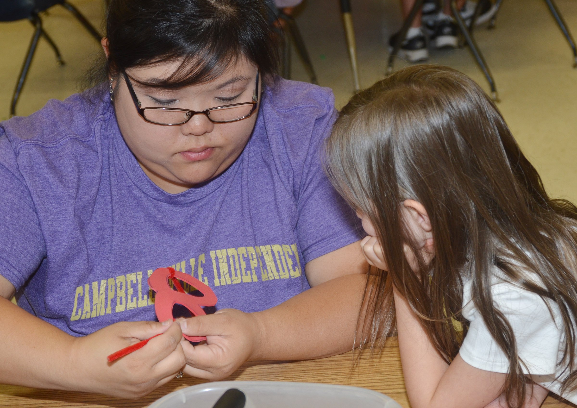CES kindergarten assistant Brittany Johnson helps Addison Perkins add pipe cleaners to her strawberry glasses.