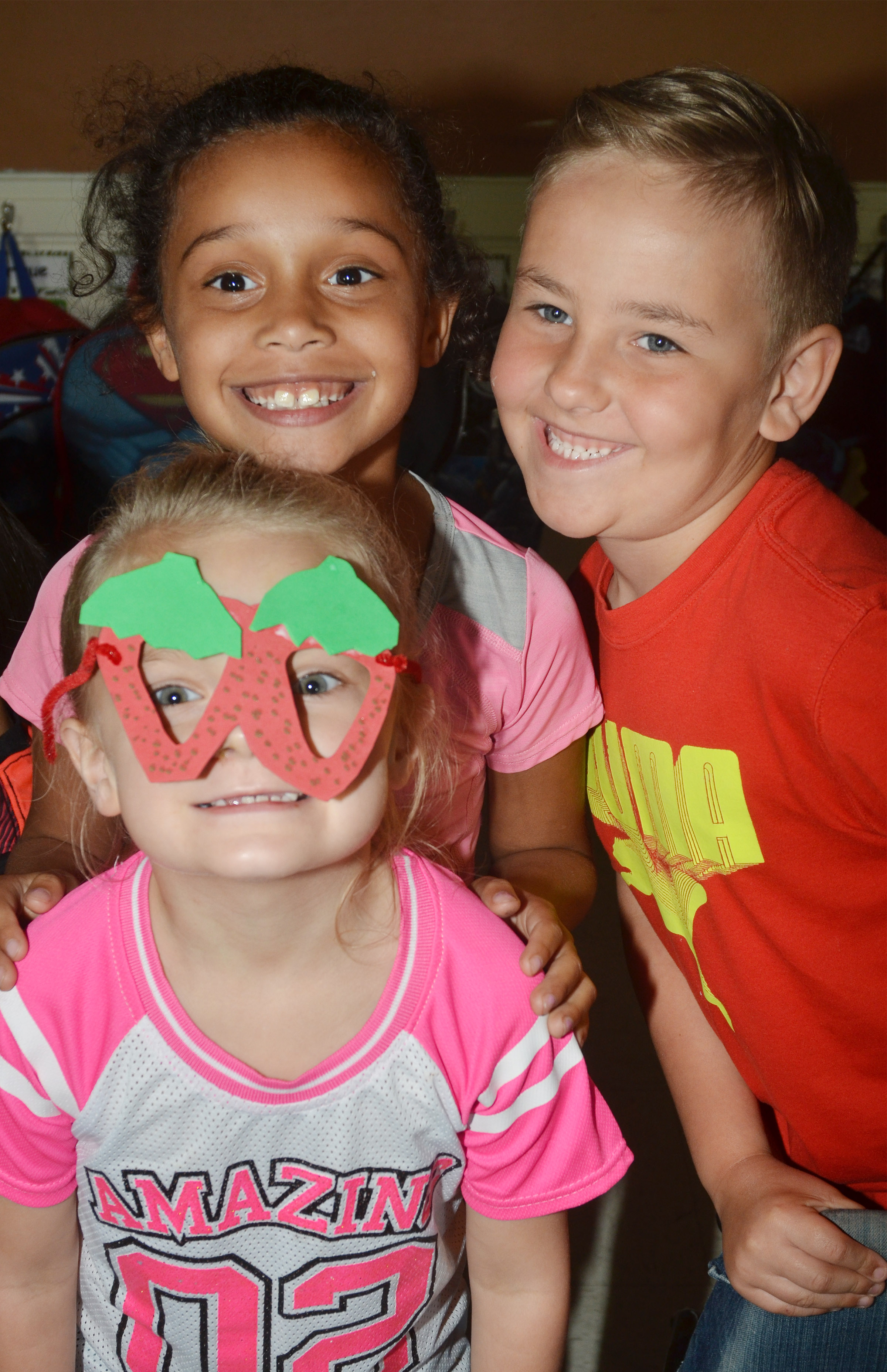 CES kindergartener Miley Orberson wears her strawberry glasses in a photo with classmates Jyra Welch and Braxton Rhodes.