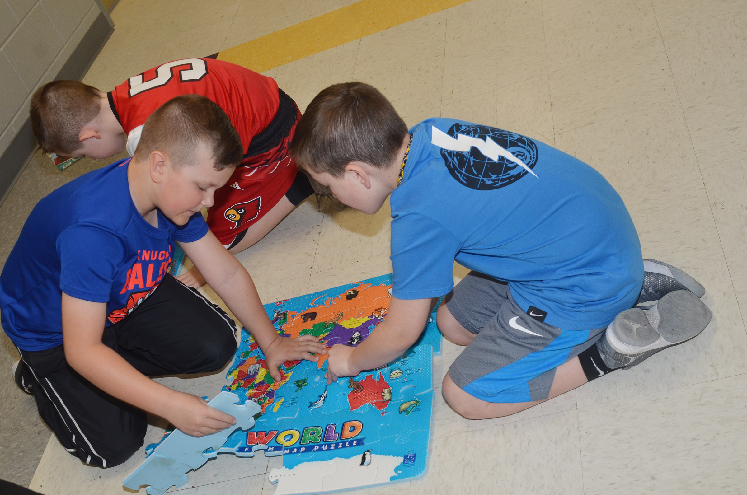 CES second-graders, from left, Cayton Lawhorn, Lanigan Price and Luke Adkins work as a team to put together a world map puzzle.