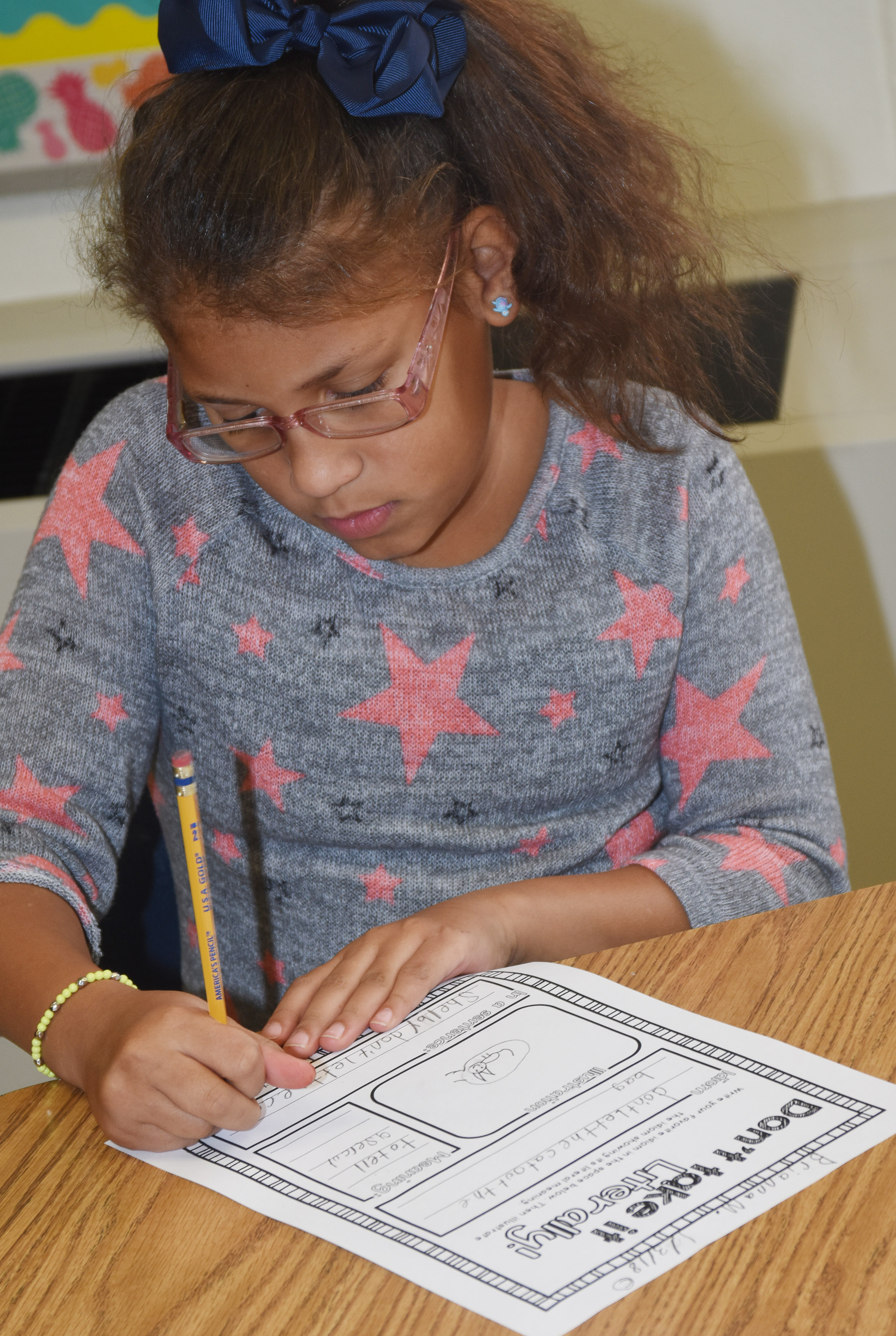 "CES fourth-grader Brianna Mitchell writes a sentence using the idiom ""don't let the cat out of the bag."""