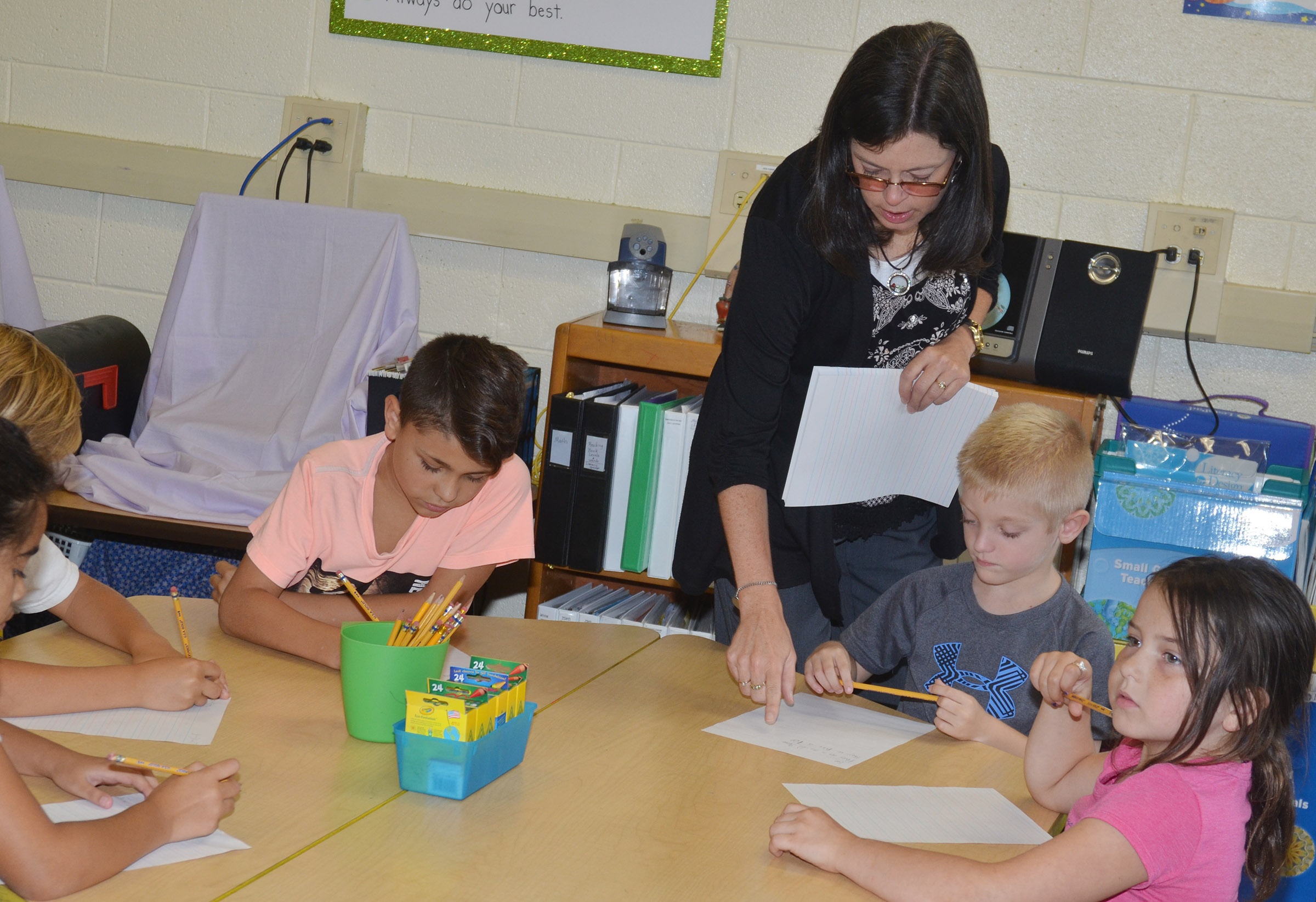 CES writing teacher Shirley Cox talks to third-grader Evan Cundiff about his writing.