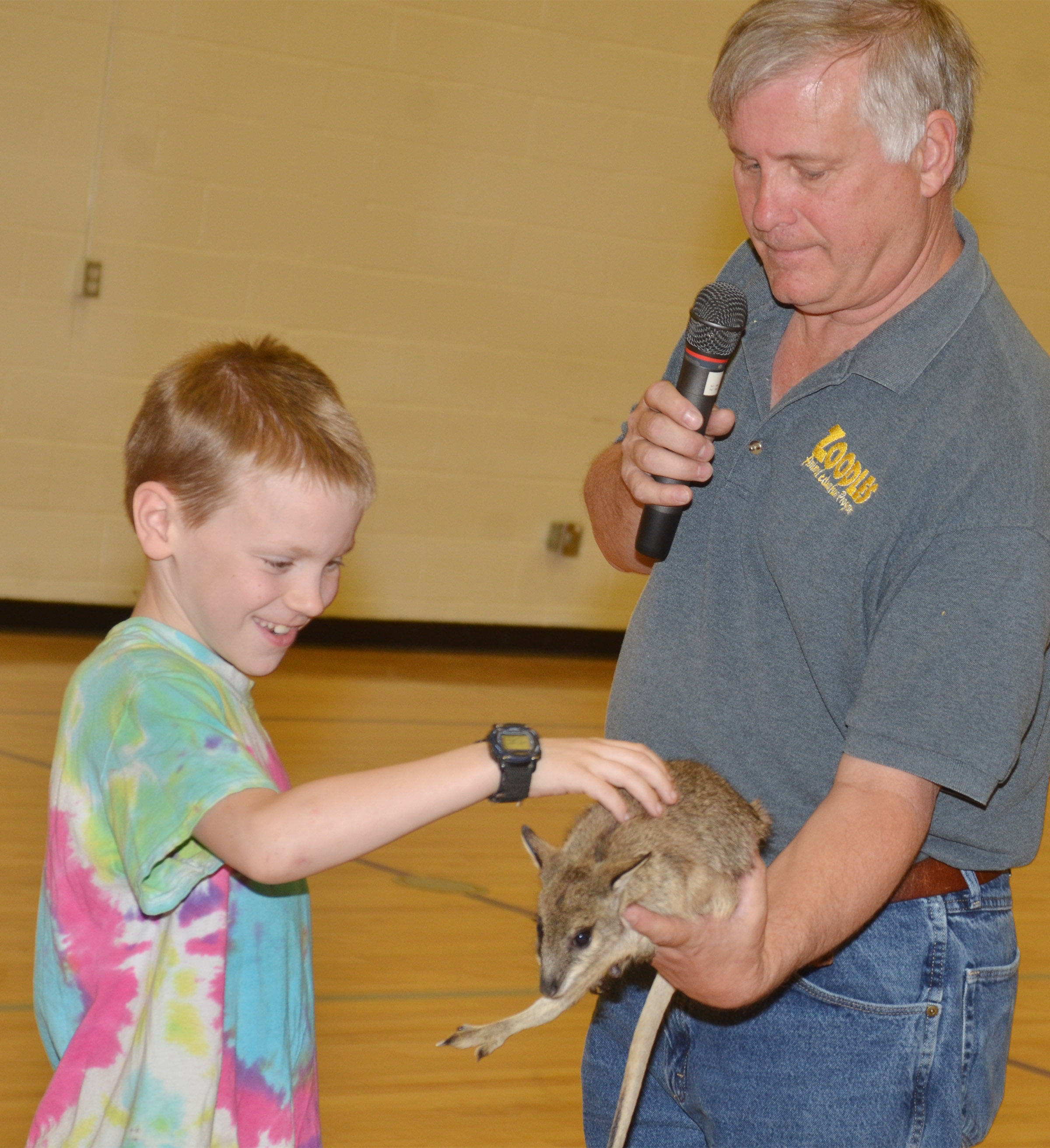 CES third-grader Connor Coots pets the baby kangaroo named Wendy, as Steven Thomas of Zoodles animal education program holds her.