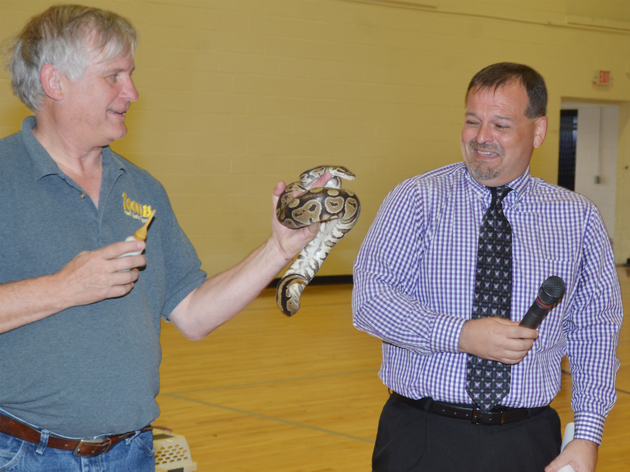 Steven Thomas of Zoodles animal education program brings Barbara the python close to CES Principal Ricky Hunt.