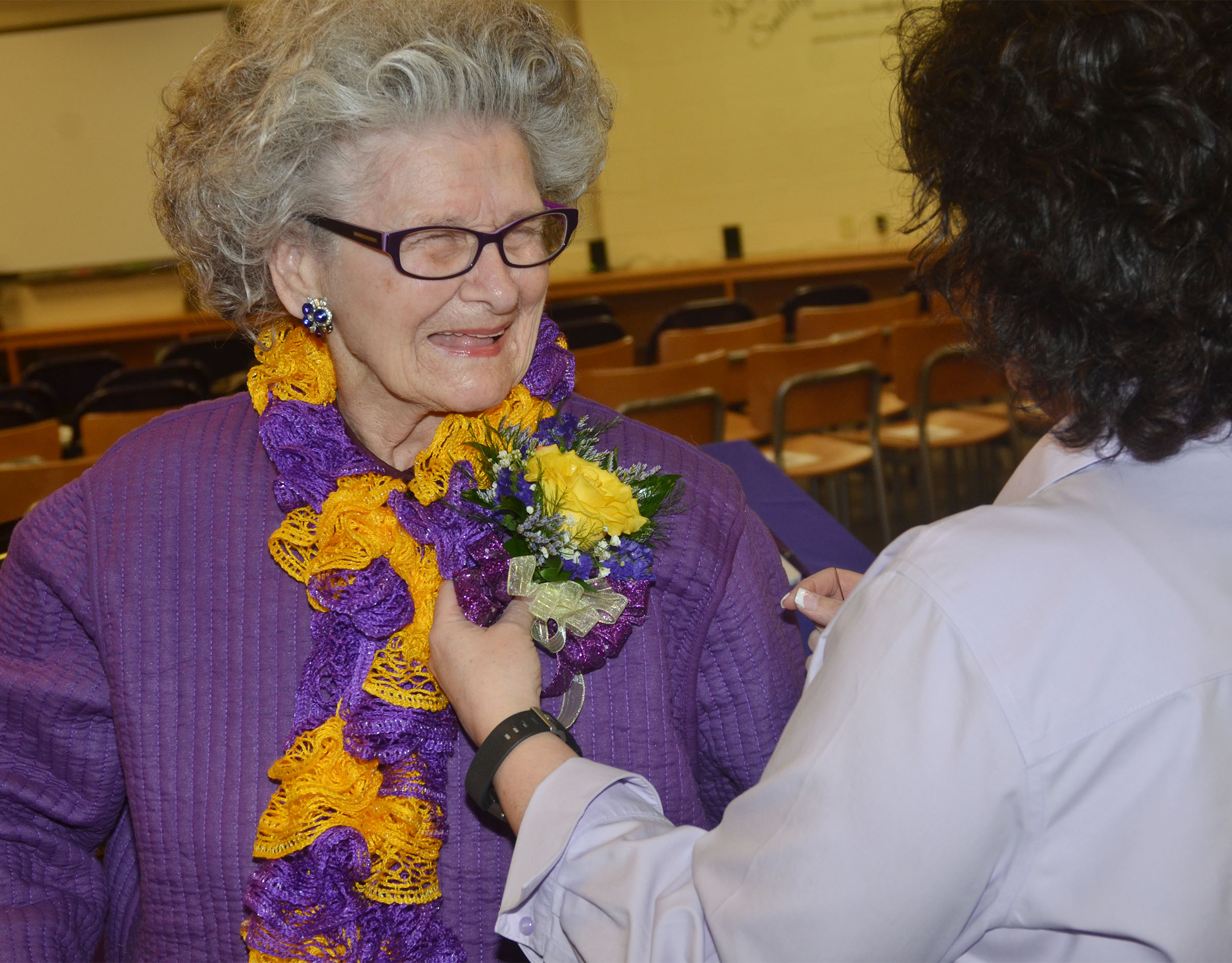 Former CHS employee Anne Fraim smiles as her corsage is pinned on her purple jacket.