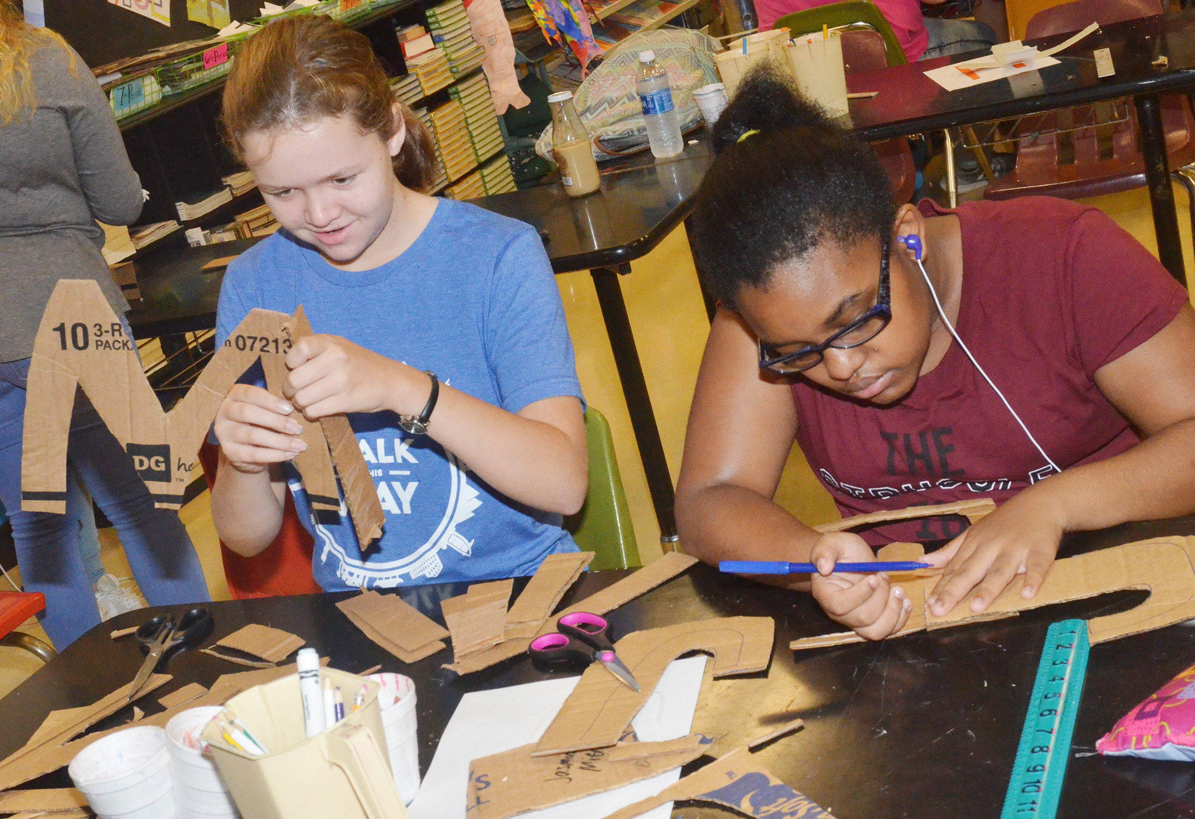 Campbellsville Middle School seventh-graders MaCayla Falls, at left, and CHS freshman Jasmine Mitchell cut out their letters.