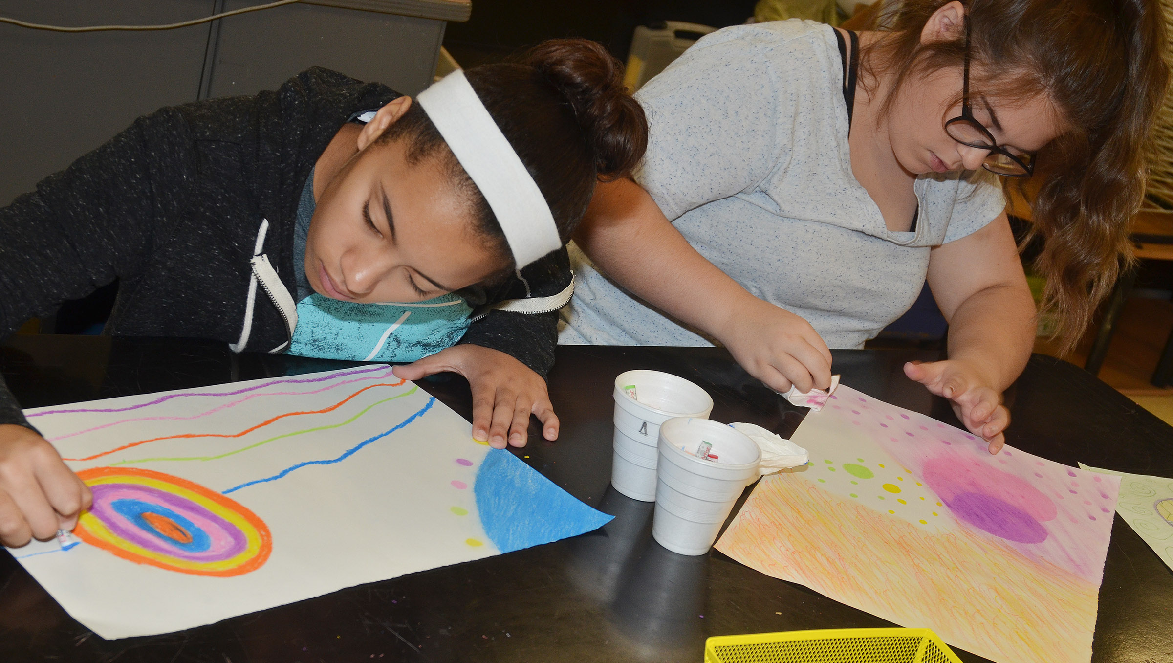 CHS freshmen Laci Hodgens, at left, and Chloe Garrett use chalk pastels on their artwork expressing emotion.