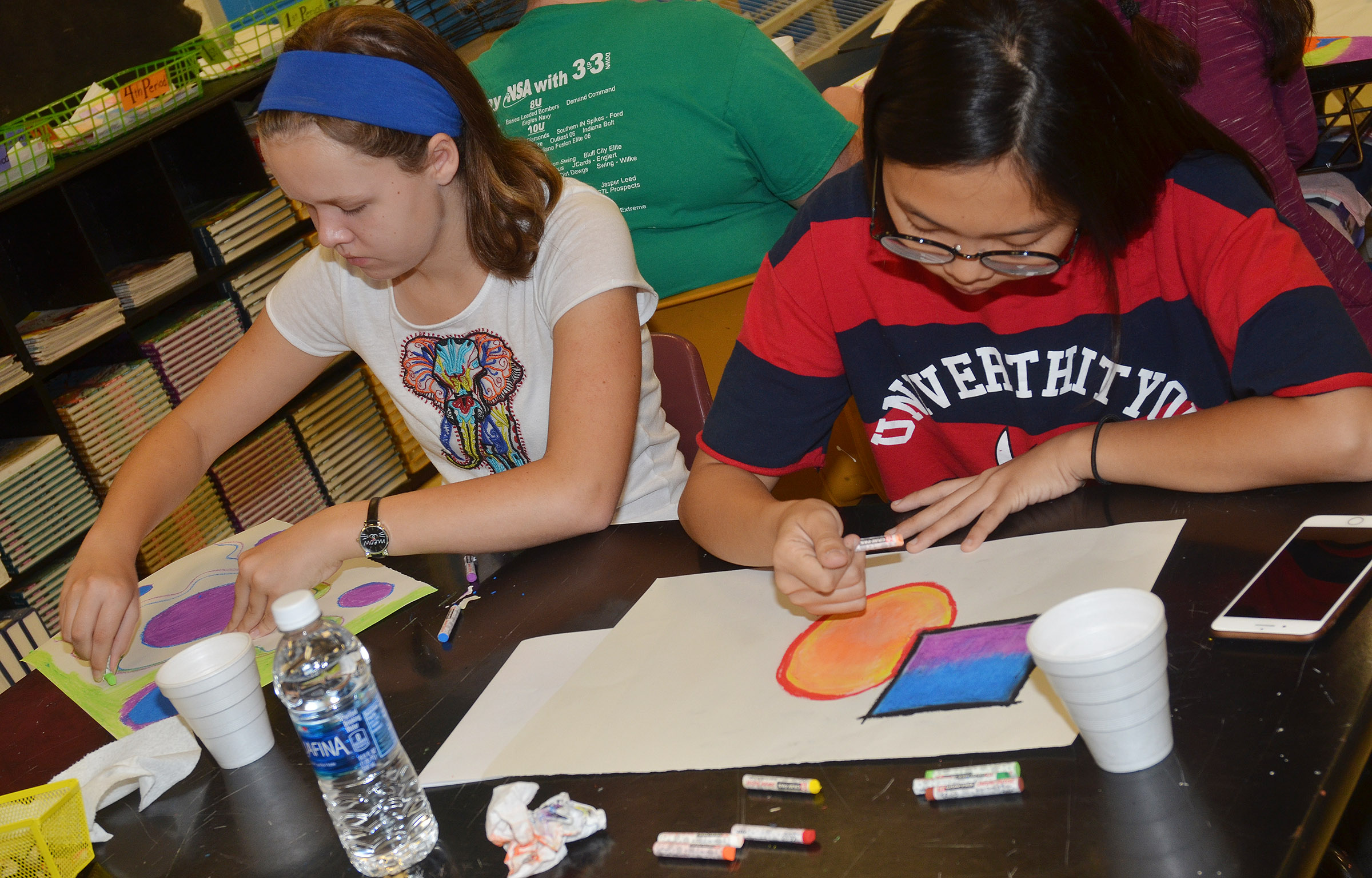 Campbellsville Middle School seventh-grader MaCayla Falls, at left, and CHS junior Annie Lee use chalk pastels on their artwork.