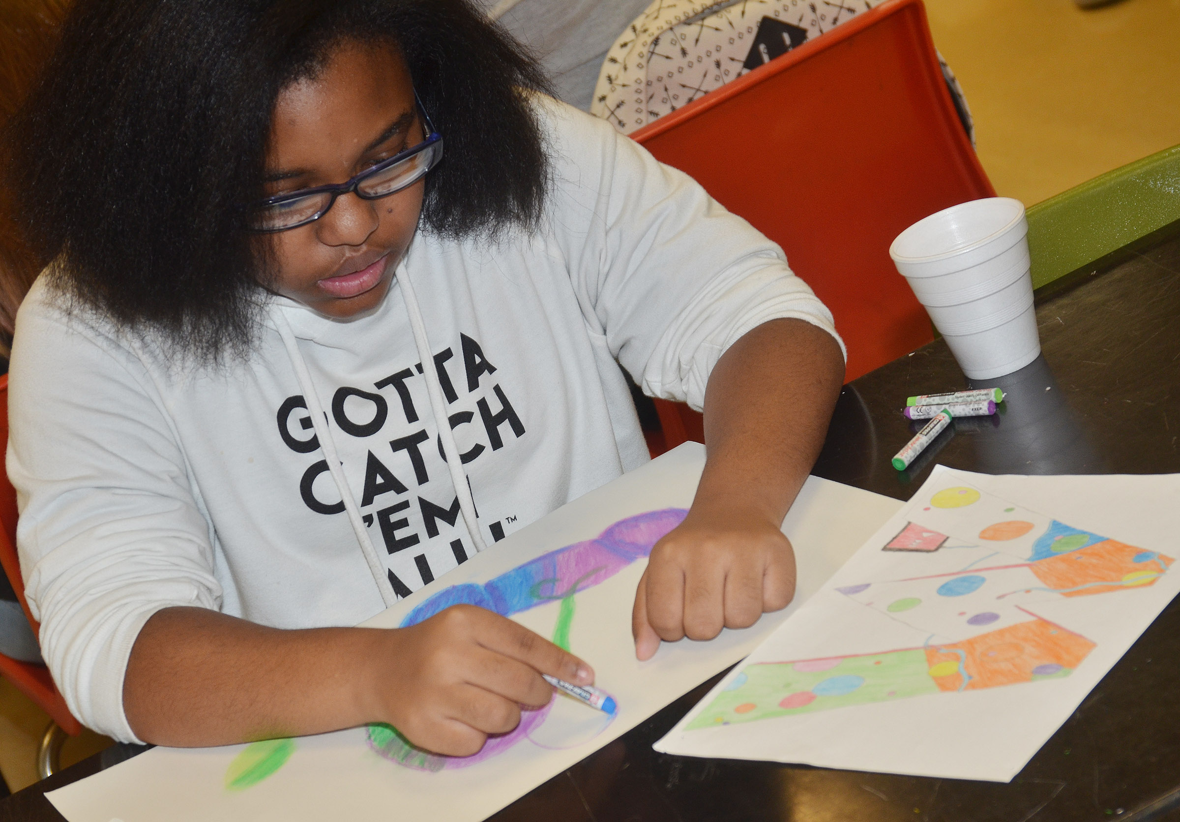 CHS freshman Jasmine Mitchell colors her drawing with chalk pastels.