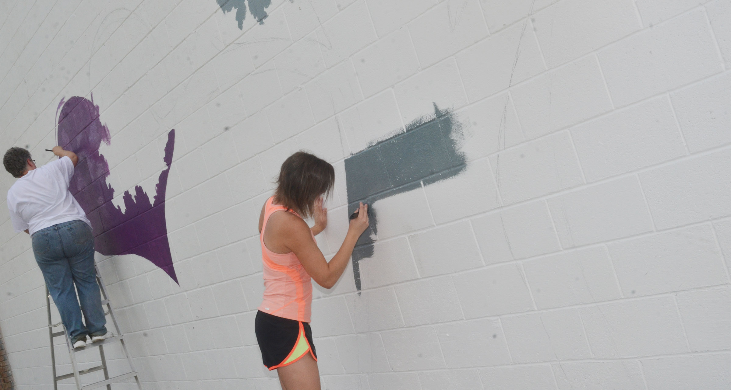 CHS art teacher Jo Ann Harris, at left, and Kyrsten Hill, who graduated in May, paint the mural.
