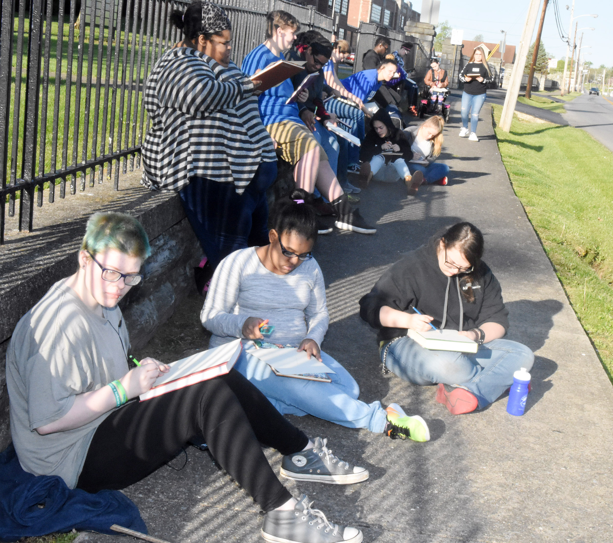 CHS art students draw outside.