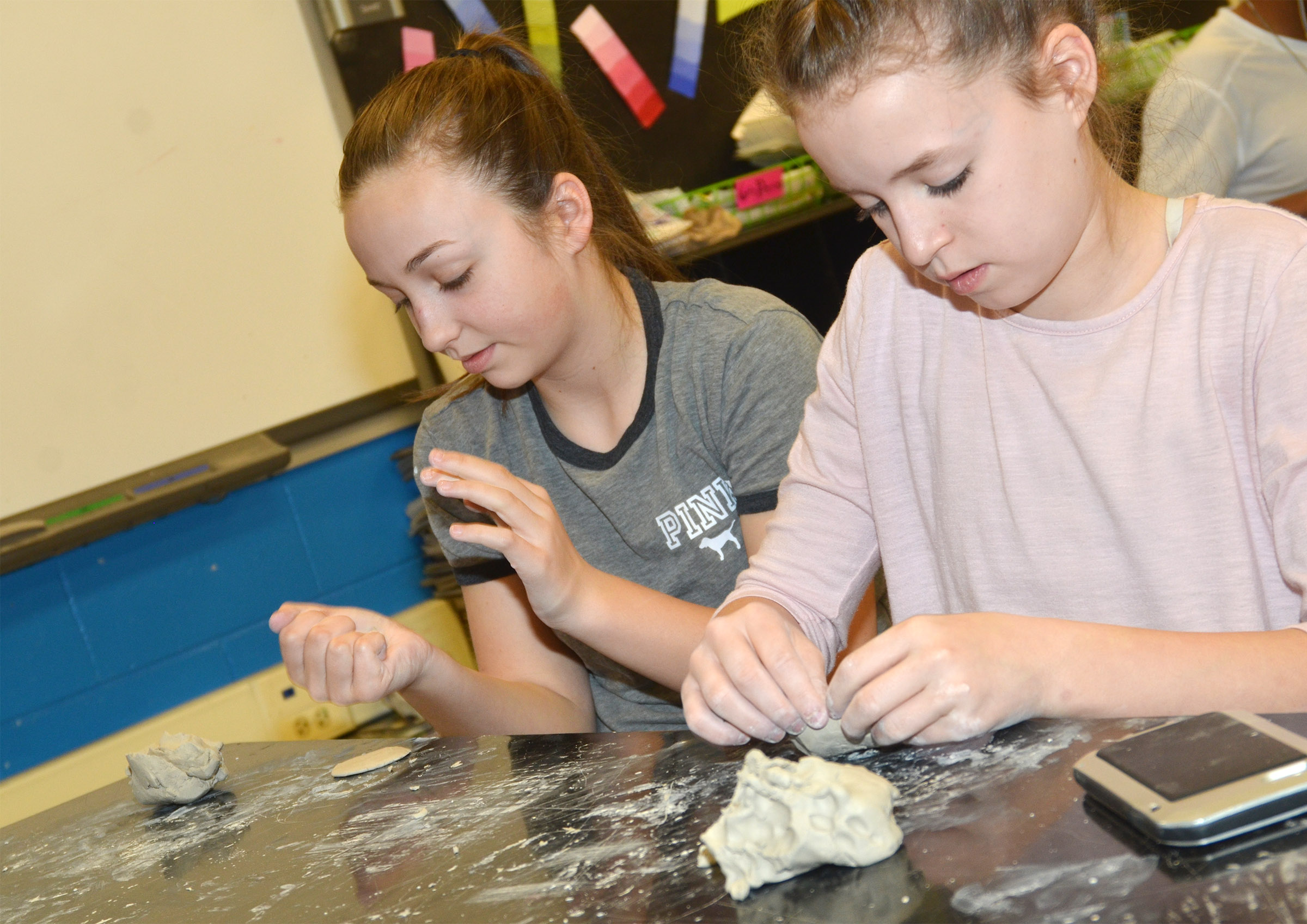 Campbellsville Middle School seventh-graders Lainey Watson, at left, and Rylee Petett shape their clay.