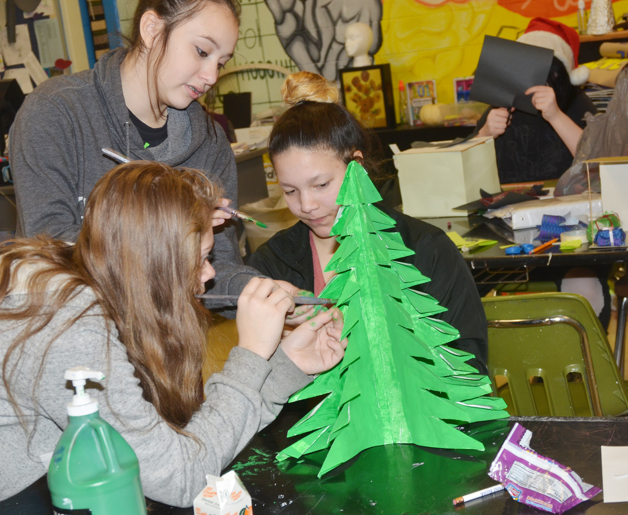 From left, CHS freshmen Emily Kerns, Victoria Garcia and Tierra Bridgewater paint a tree for a model of their set design.