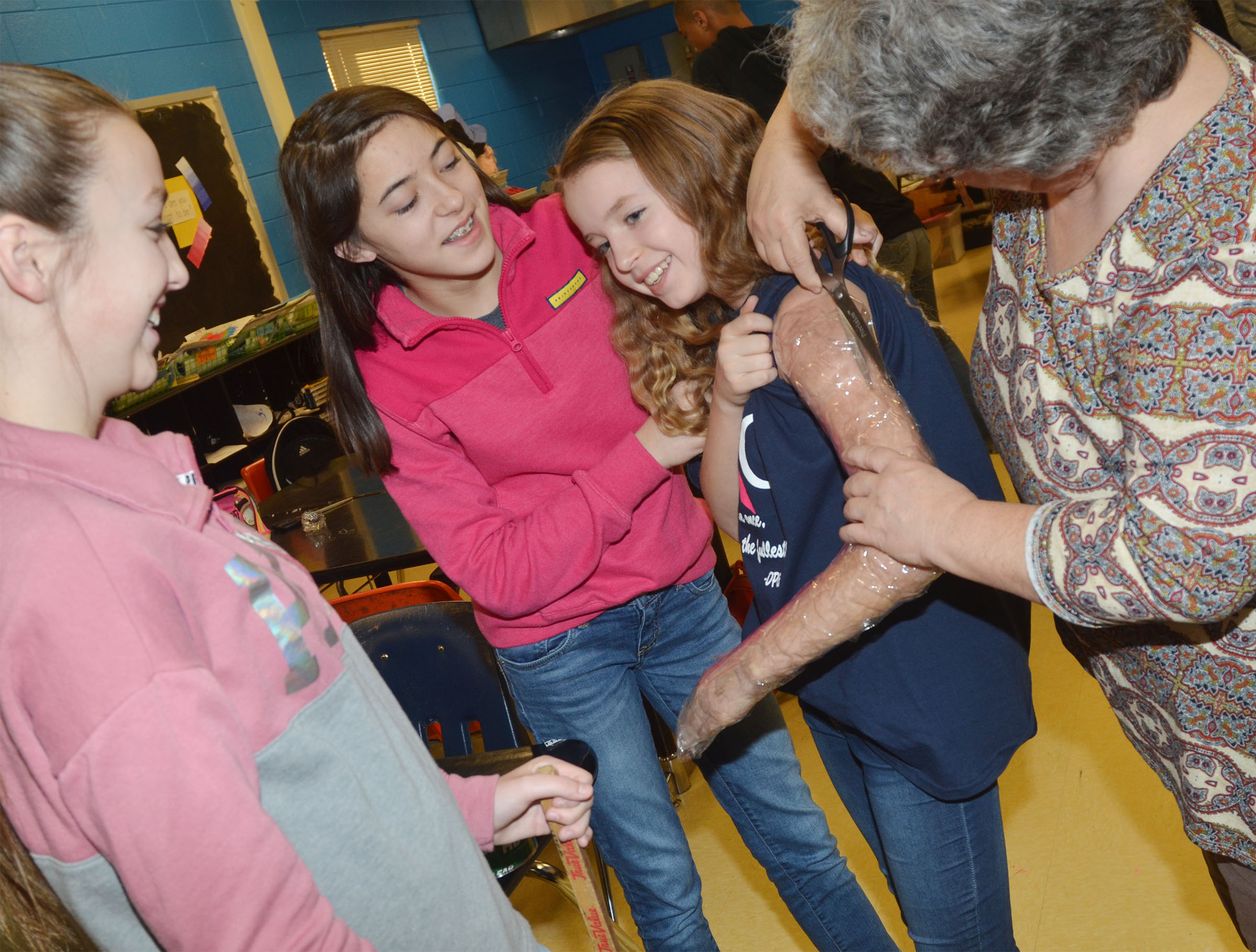 CHS art teacher Jo Ann Harris, at right, helps Campbellsville Middle School seventh-graders, from left, Lainey Watson, Kaylyn Smith and Rylee Petett as Petett's arm is cut out after it is taped.