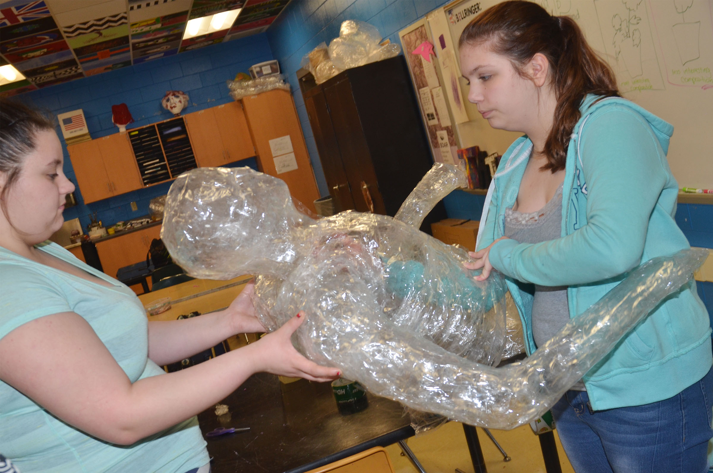 CHS sophomore Amanda Dotson, at left, and freshman Shelby Hunt put their tape person together.