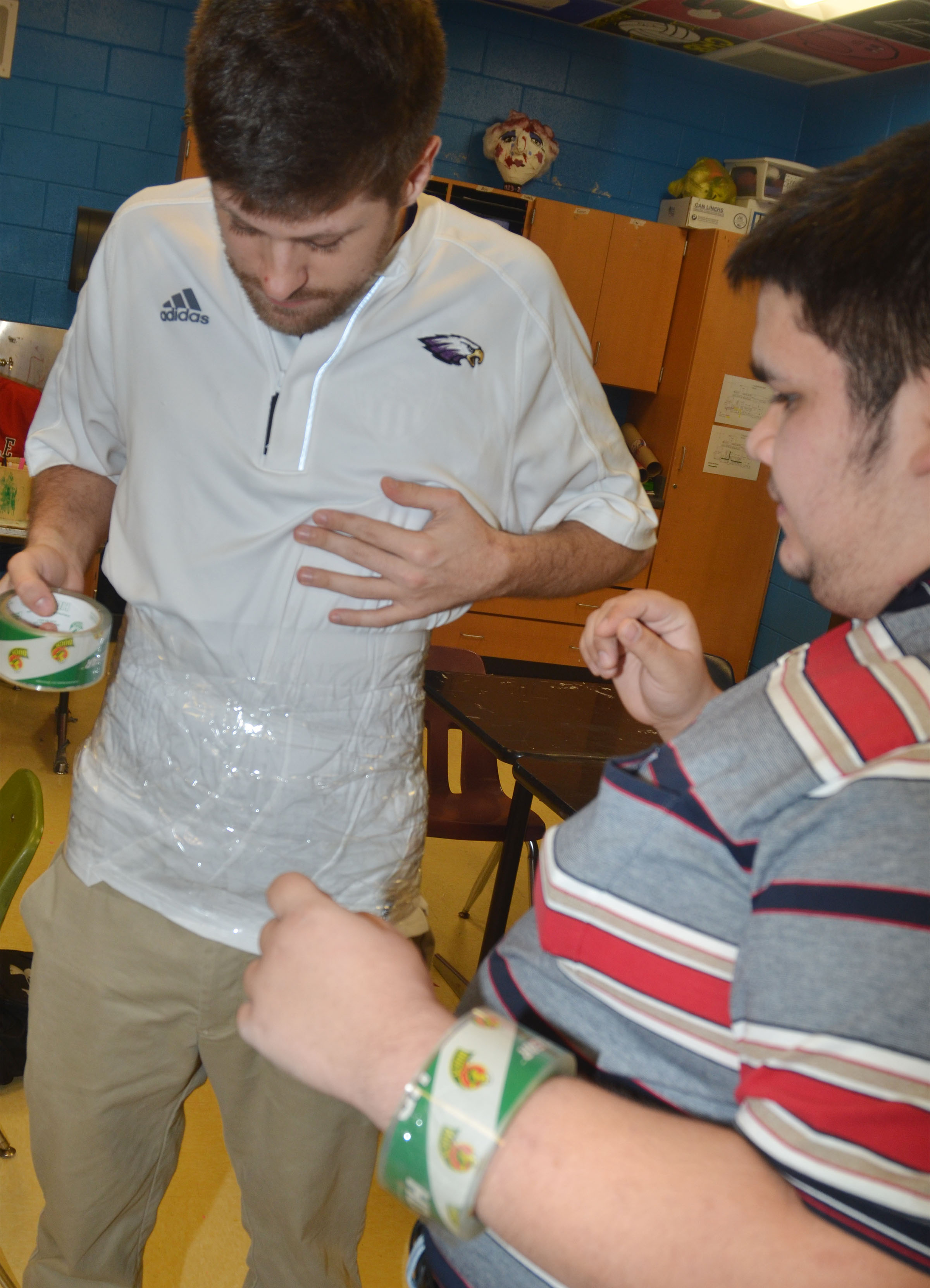 CHS instructional assistant Matthew Schmuck tapes his torso, with some help from CHS senior Robert Tungate.