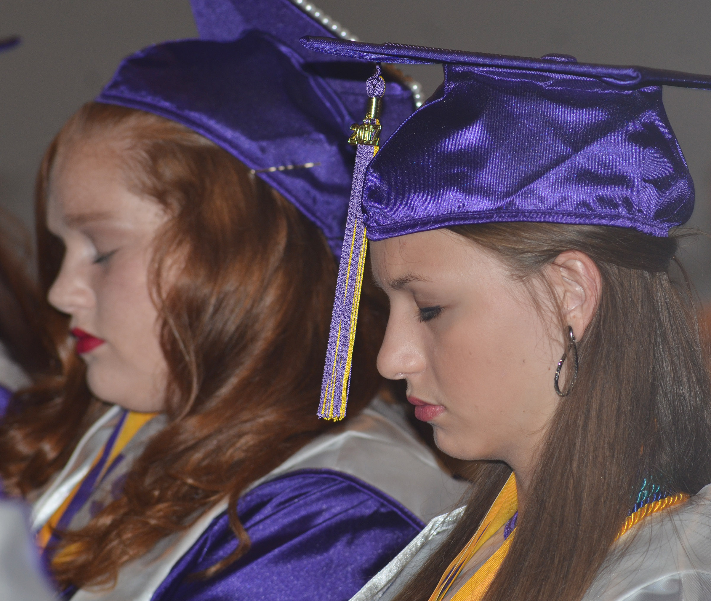 CHS seniors Mallory Haley, at left, and Caylie Blair pray during the baccalaureate ceremony.