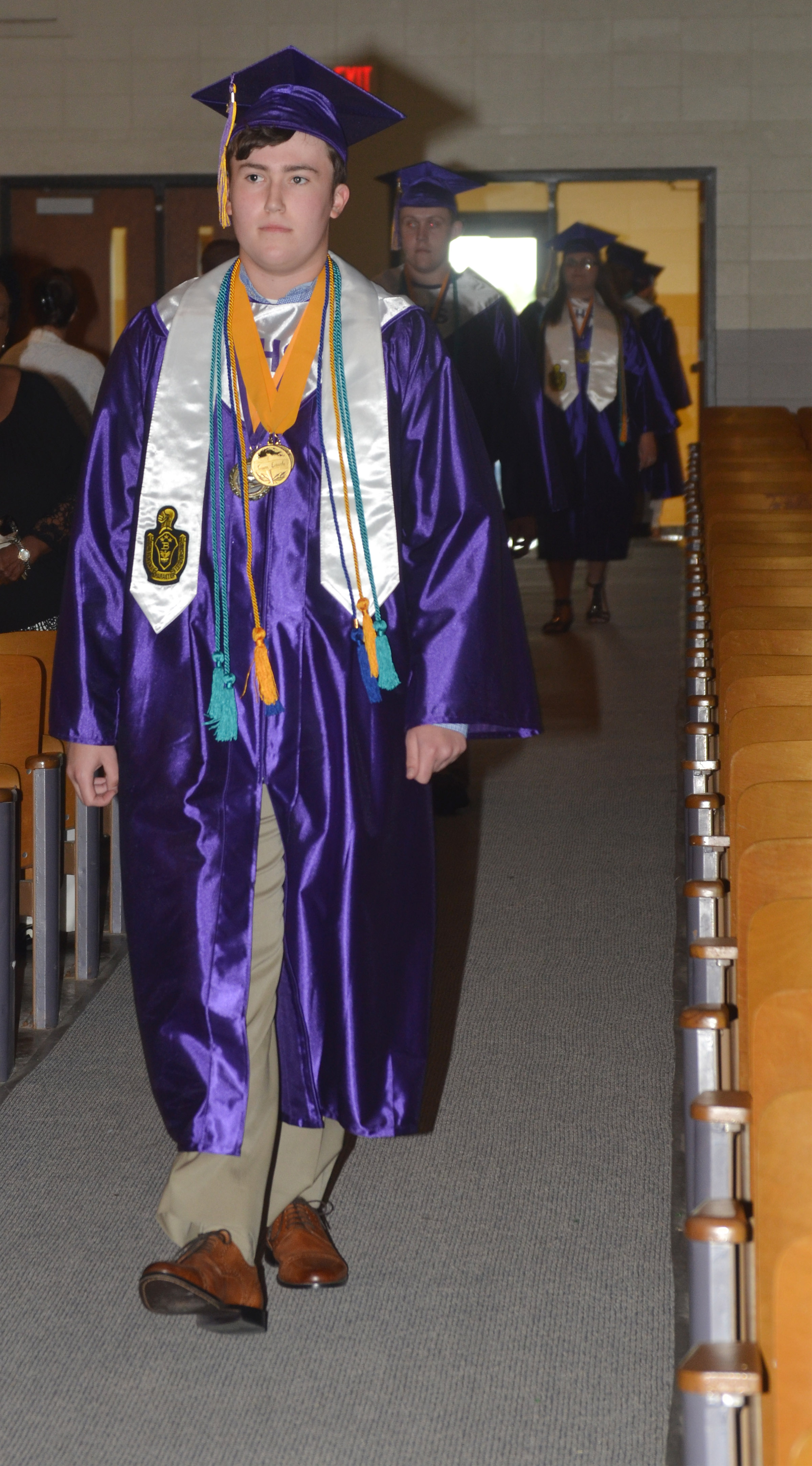 CHS senior Zack Settle walks in Hamilton Auditorium for the baccalaureate ceremony.