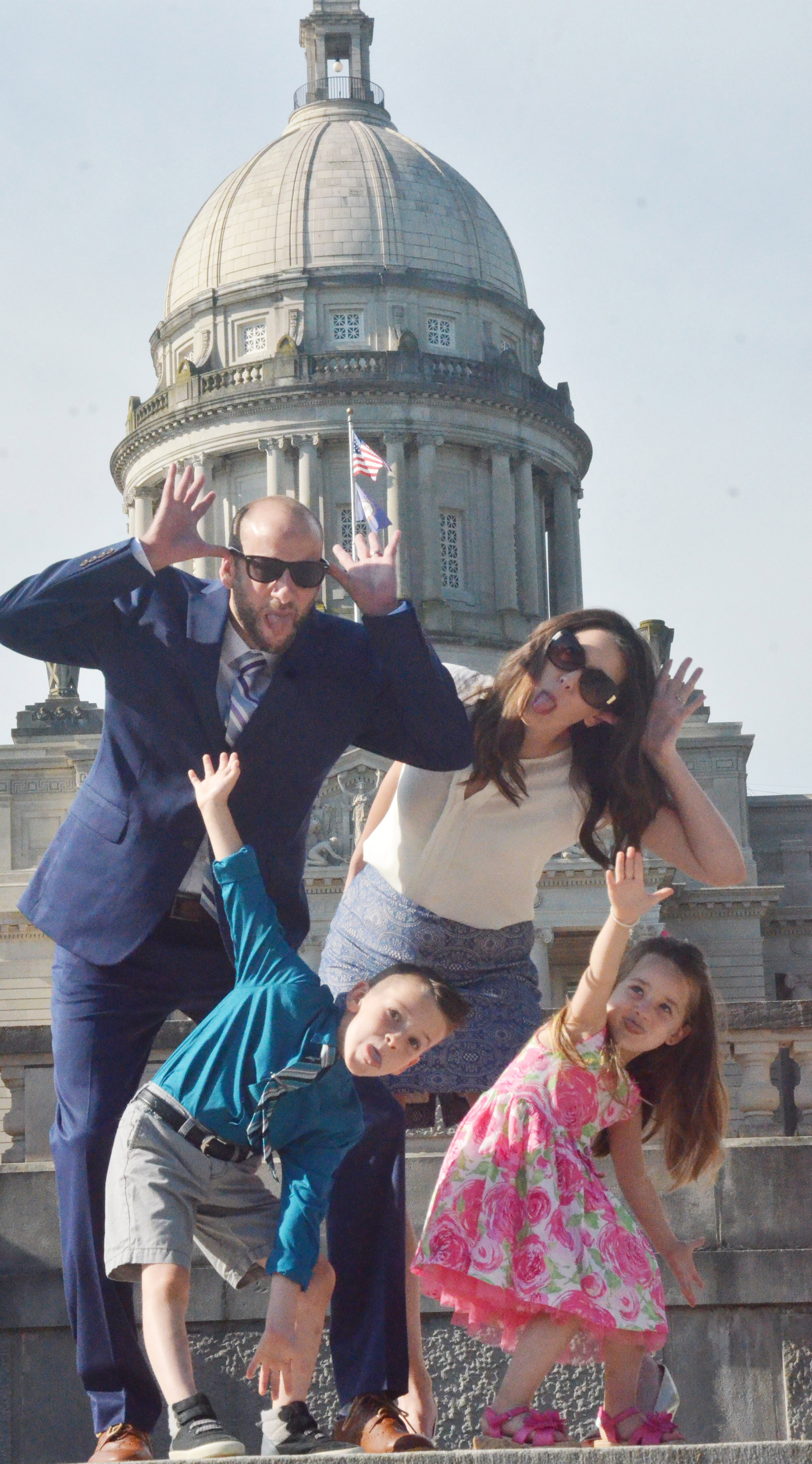 CHS teacher Ben Davis and his wife, Stephanie, pose for a silly photo in front of the Kentucky capitol with their children Cash and Lylah.