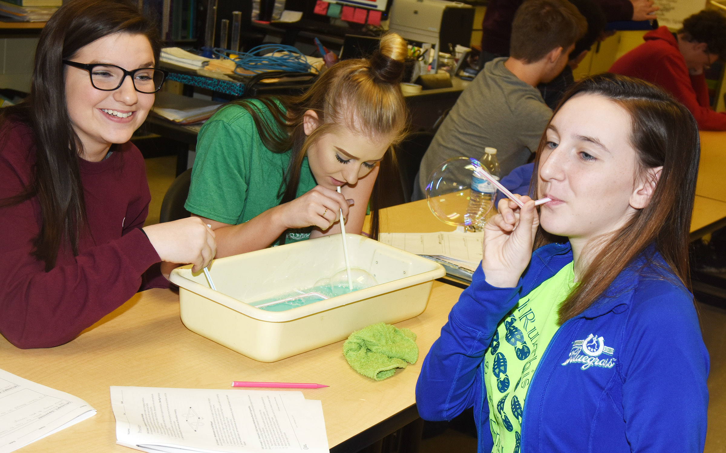 CHS sophomore Zoe McAninch blows a bubble as classmates Sydney Wilson, at left, and Isabella Osborne watch.