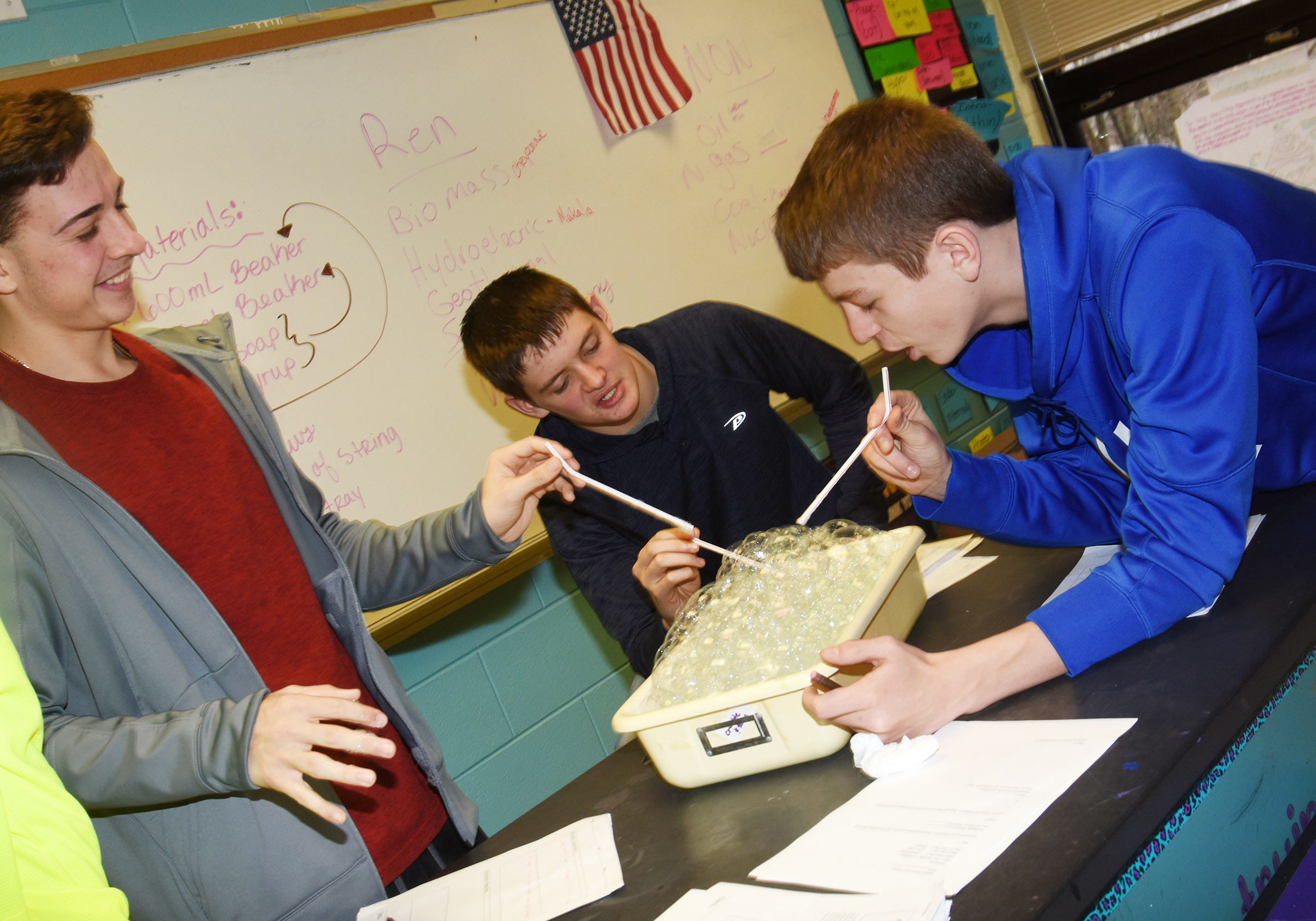 From left, CHS freshman John Orberson and sophomores Blake Allen and Noah Hughes blow bubbles as they conduct their cell membrane lab exercise.