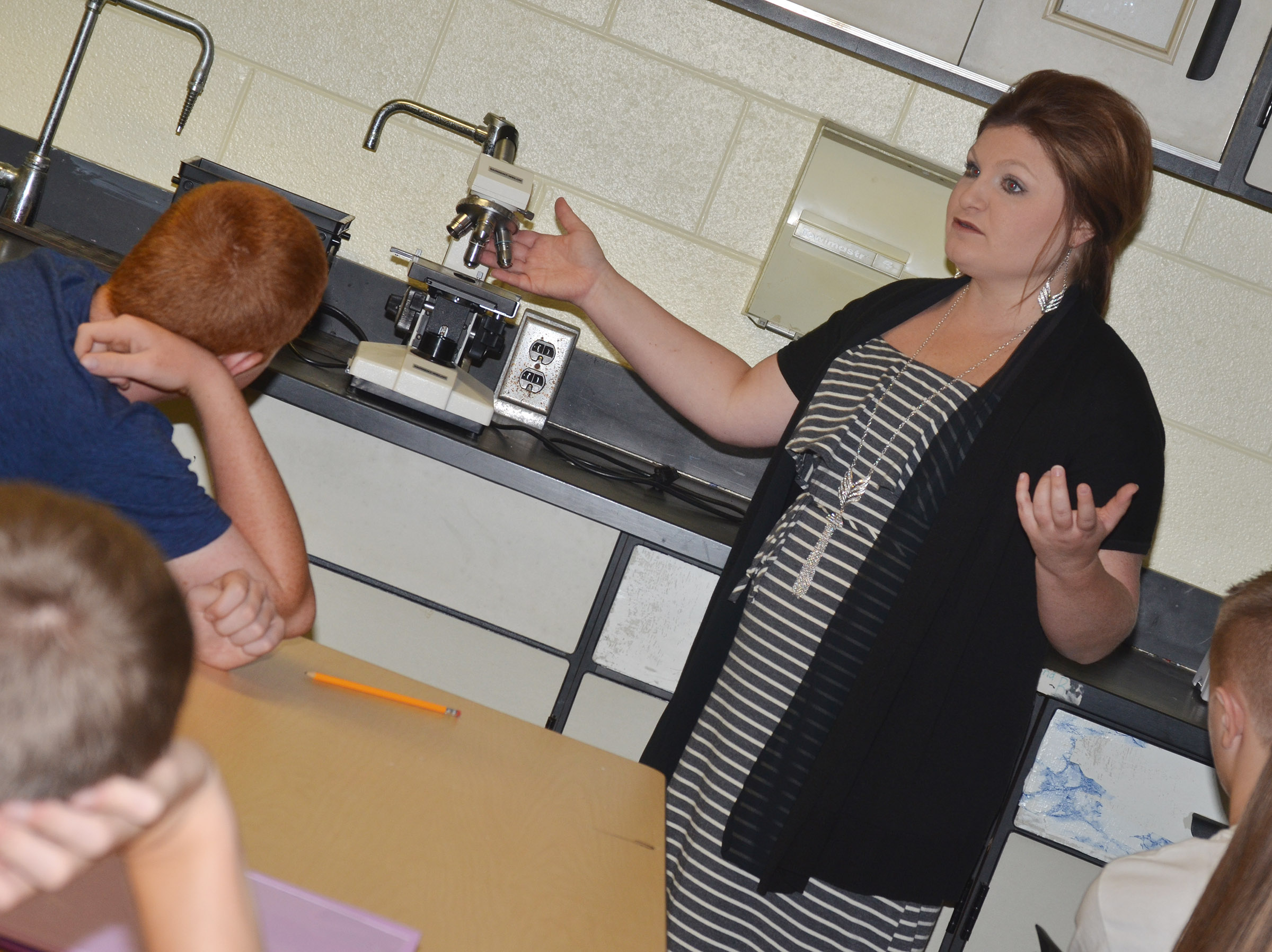 CHS teacher Lauren Bennett talks to her AP biology students about the proper way to use a microscope.
