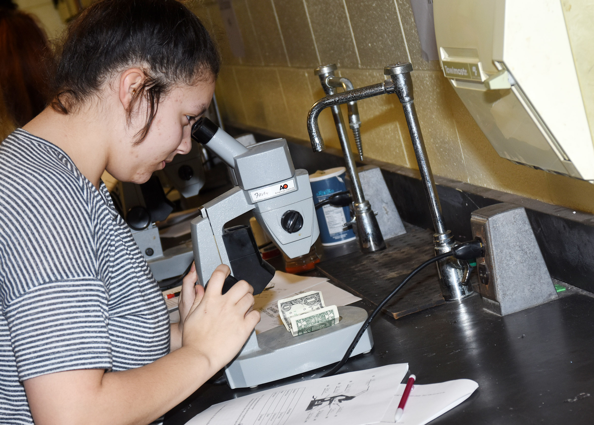 CHS freshman Tierra Bridgewater looks at a $1 bill under the microscope.