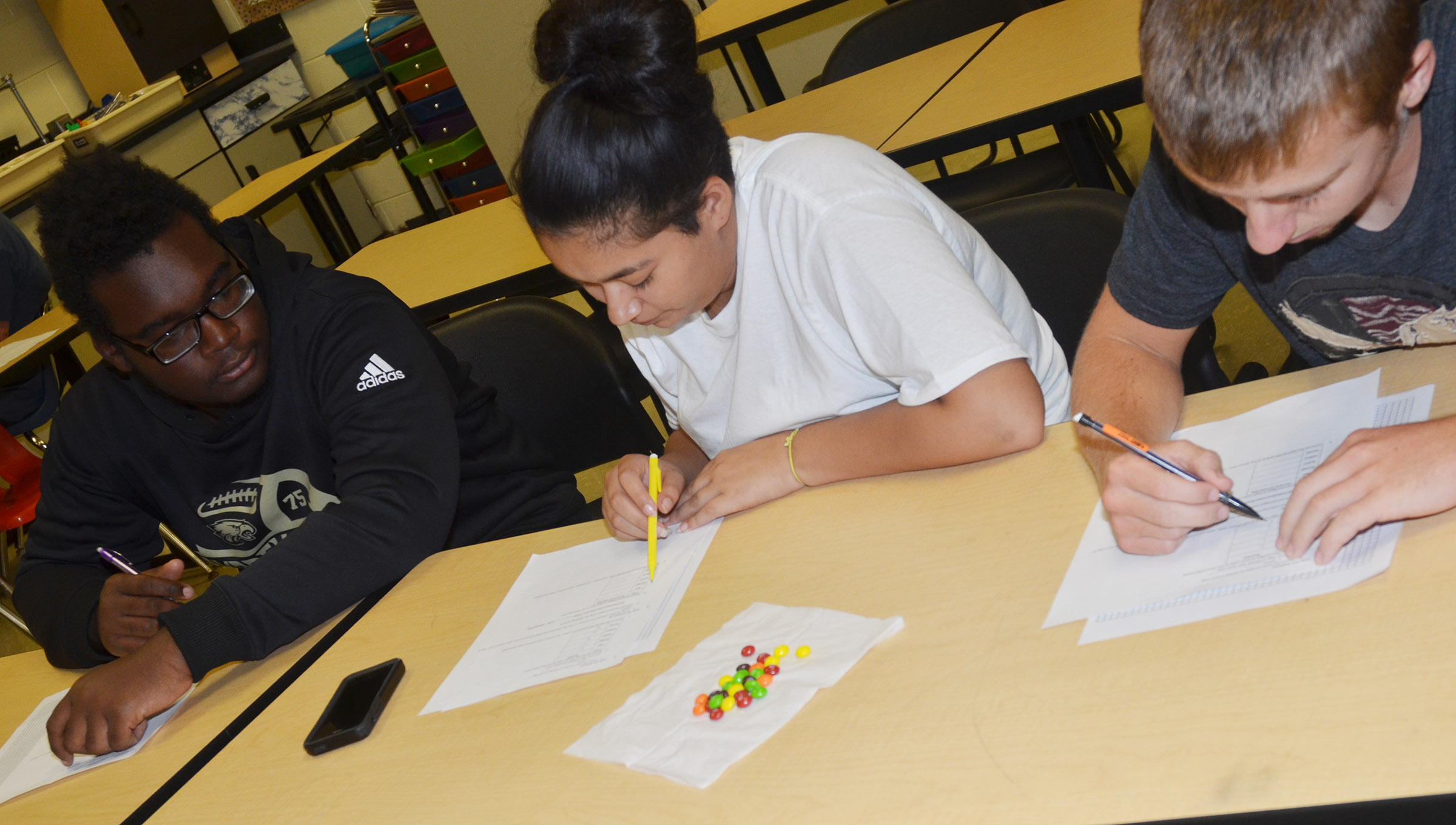 From left, CHS sophomores Taekwon McCoy, Cristina Barrera and Michael Griffiths sort their Skittles candies and create their graph to represent how many they have of each color.