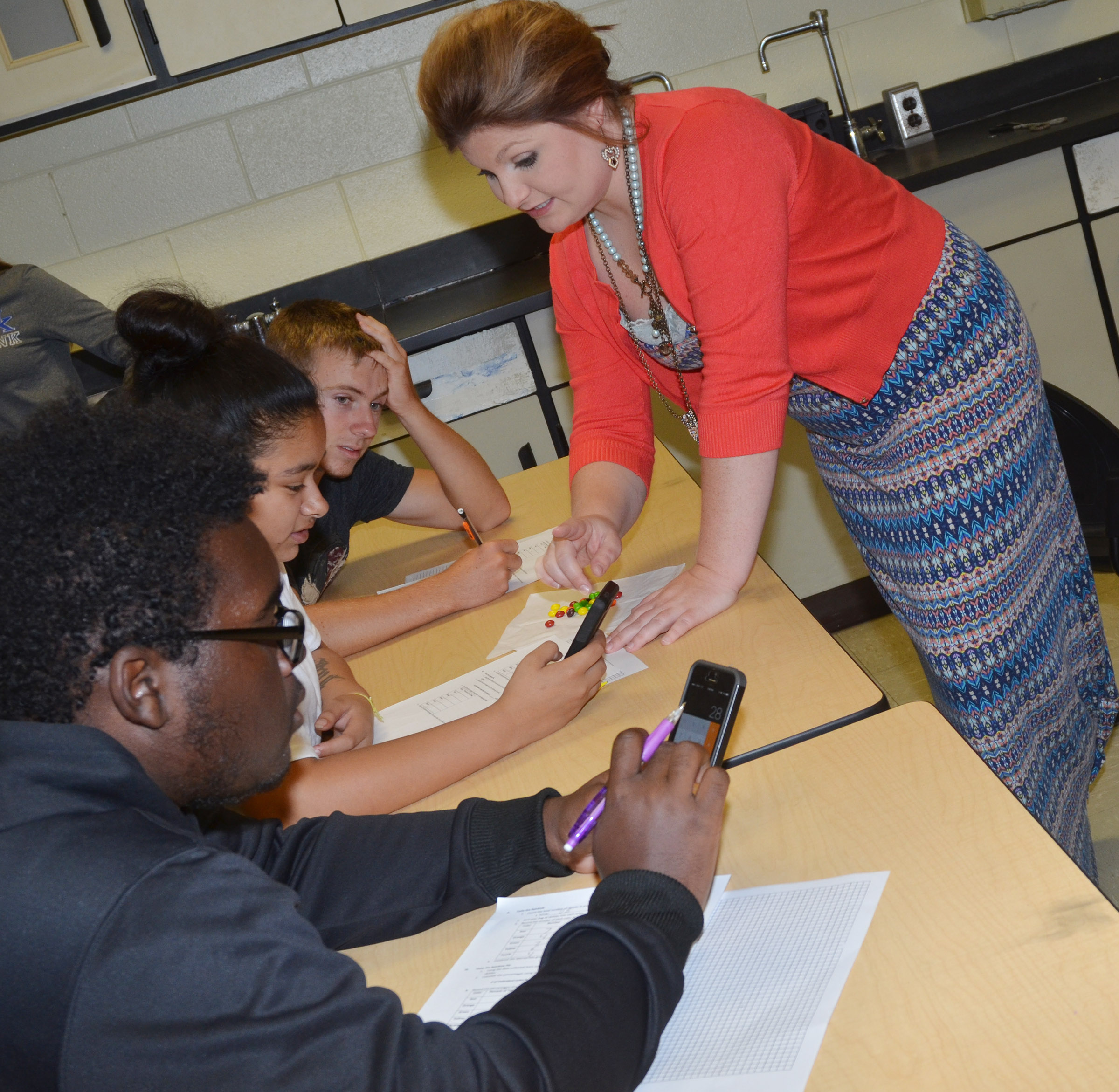 CHS teacher Lauren Bennett helps sophomores, from left, Taekwon McCoy, Cristina Barrera and Michael Griffiths as they create their graphs.
