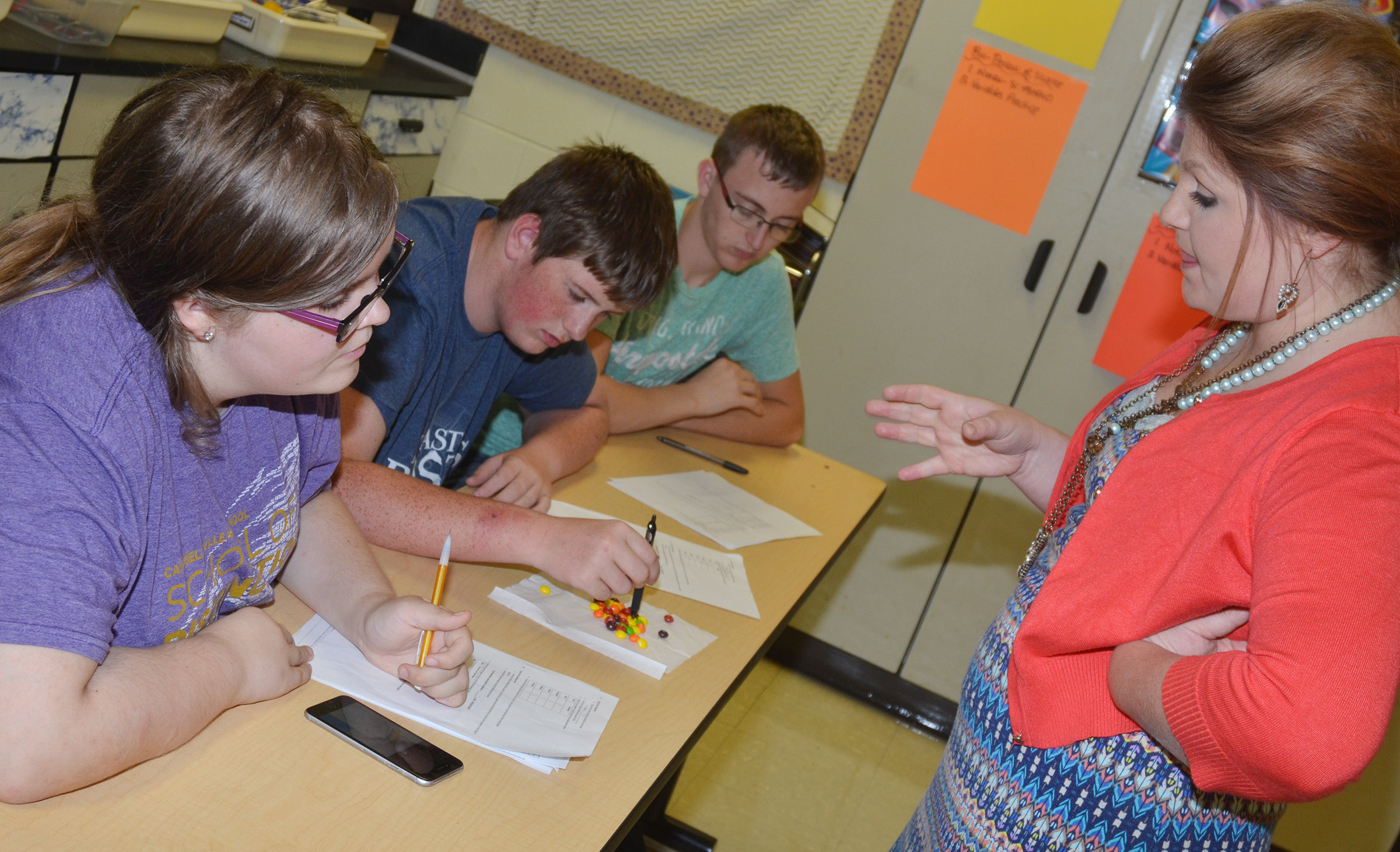 CHS teacher Lauren Bennett helps, from left, sophomore Taylor Brewer and juniors Quentin Skaggs and Josh Mahan as they count and sort their Skittles.