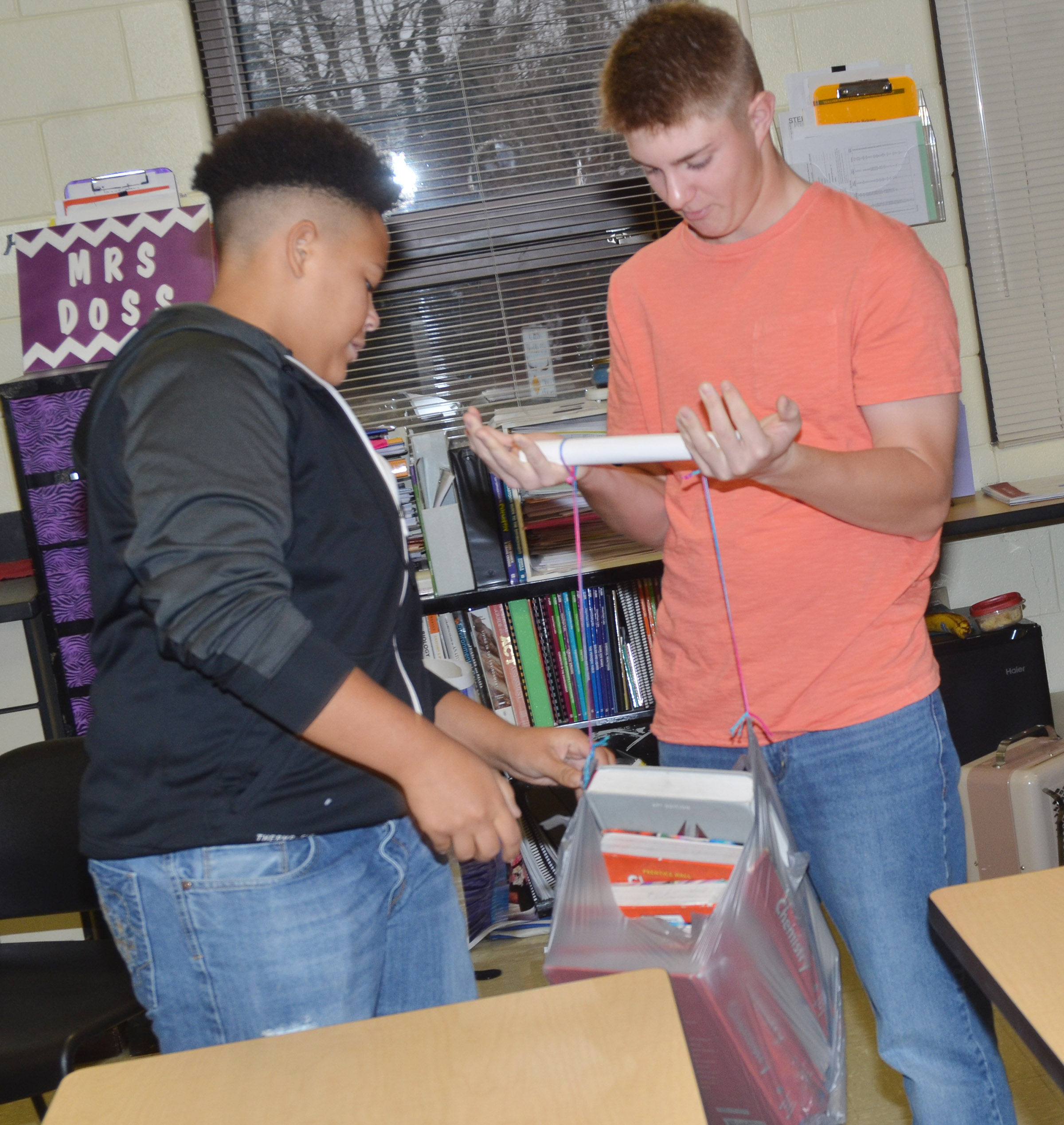 "CHS sophomore Dee Simpson, at left, and junior Alex Doss see how many books can be added to the bag with the ""bone"" absorbing the force."