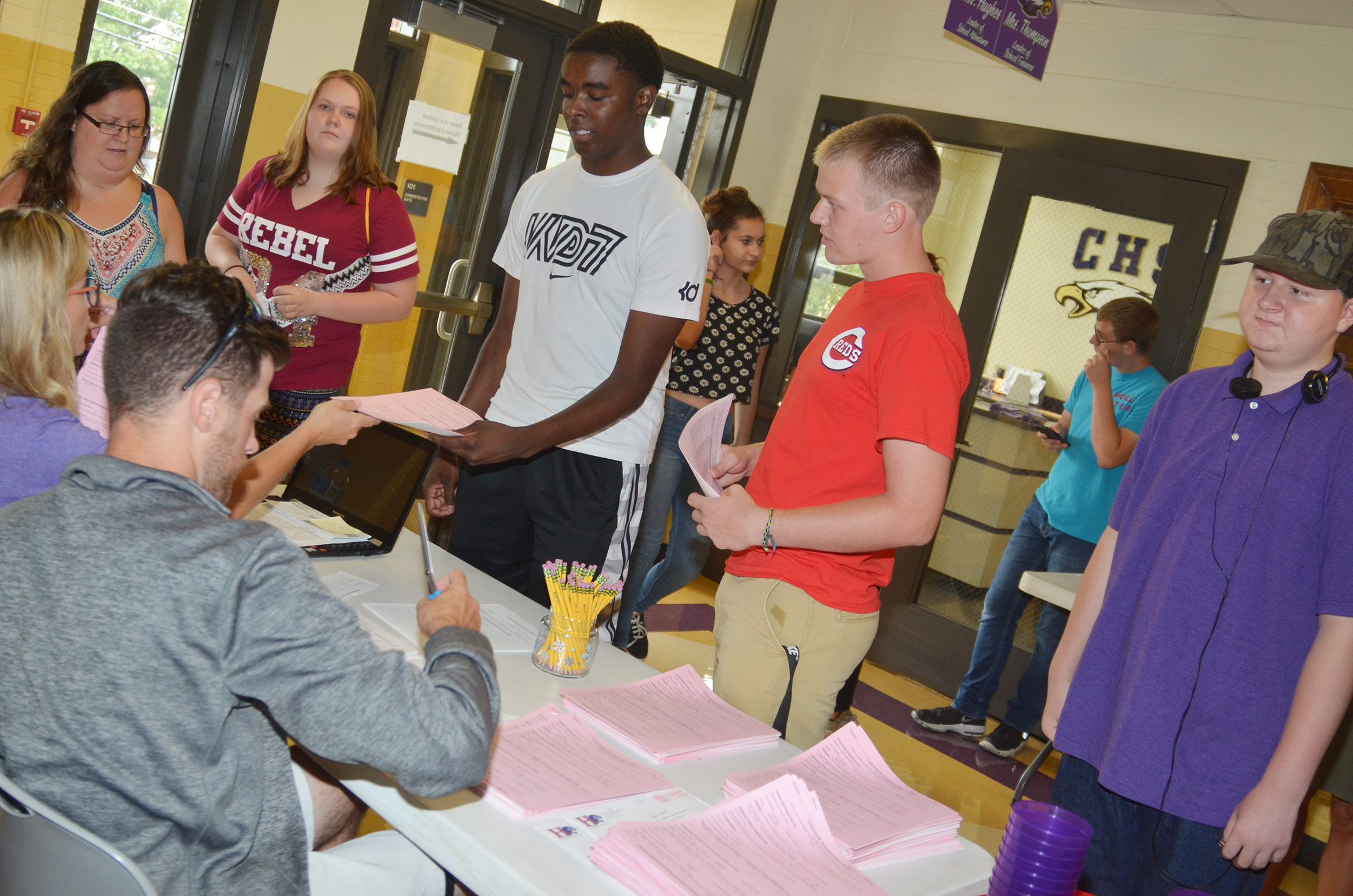CHS seniors Chanson Atkinson and Wyatt Houk, center, receive their schedules.