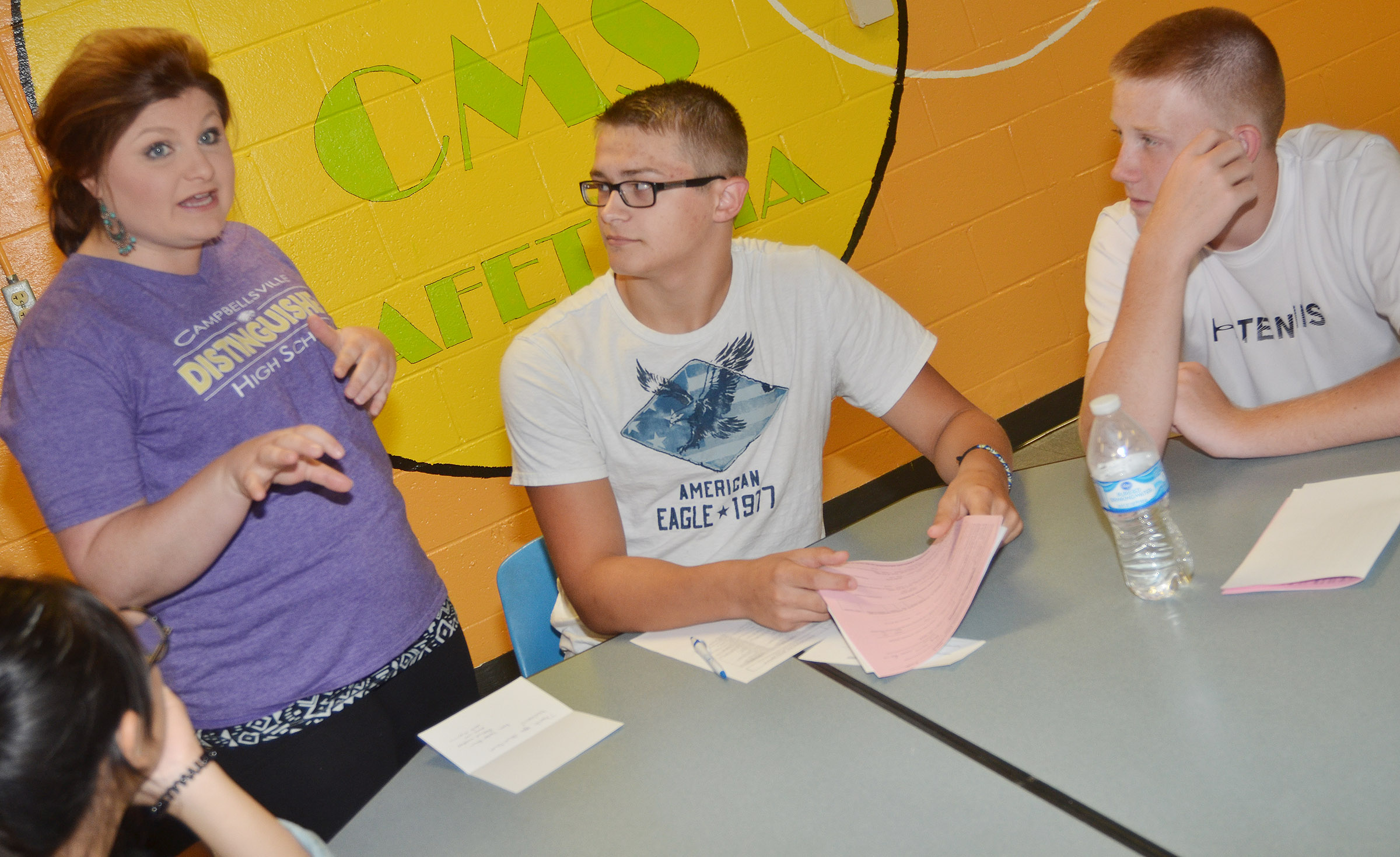 CHS teacher Lauren Bennett talks with CHS sophomores Dalton Brown, center, and Patrick Walker about their community service project.
