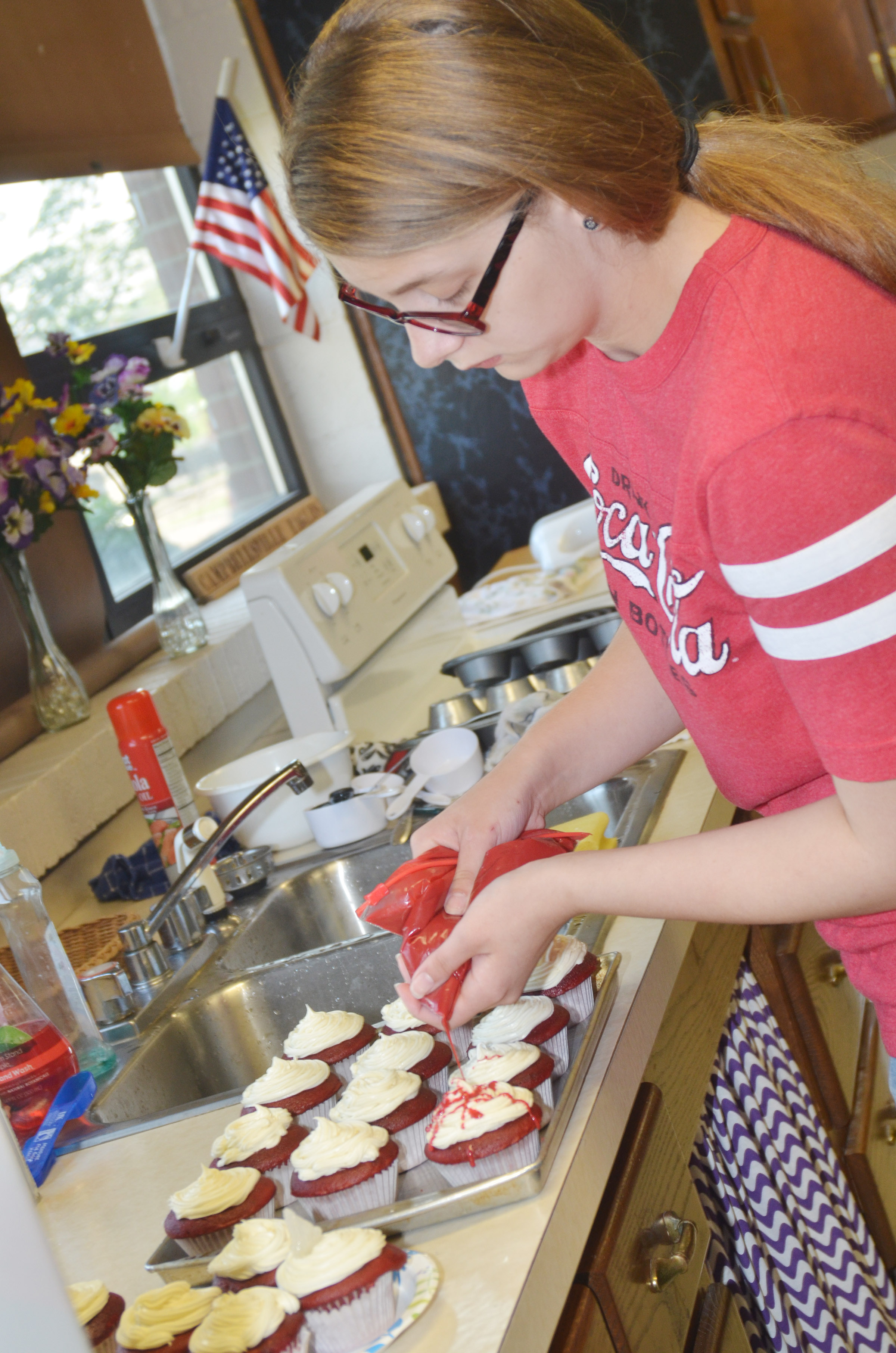 CHS senior Alexis Underwood decorates the red velvet cupcakes she made for her final project.