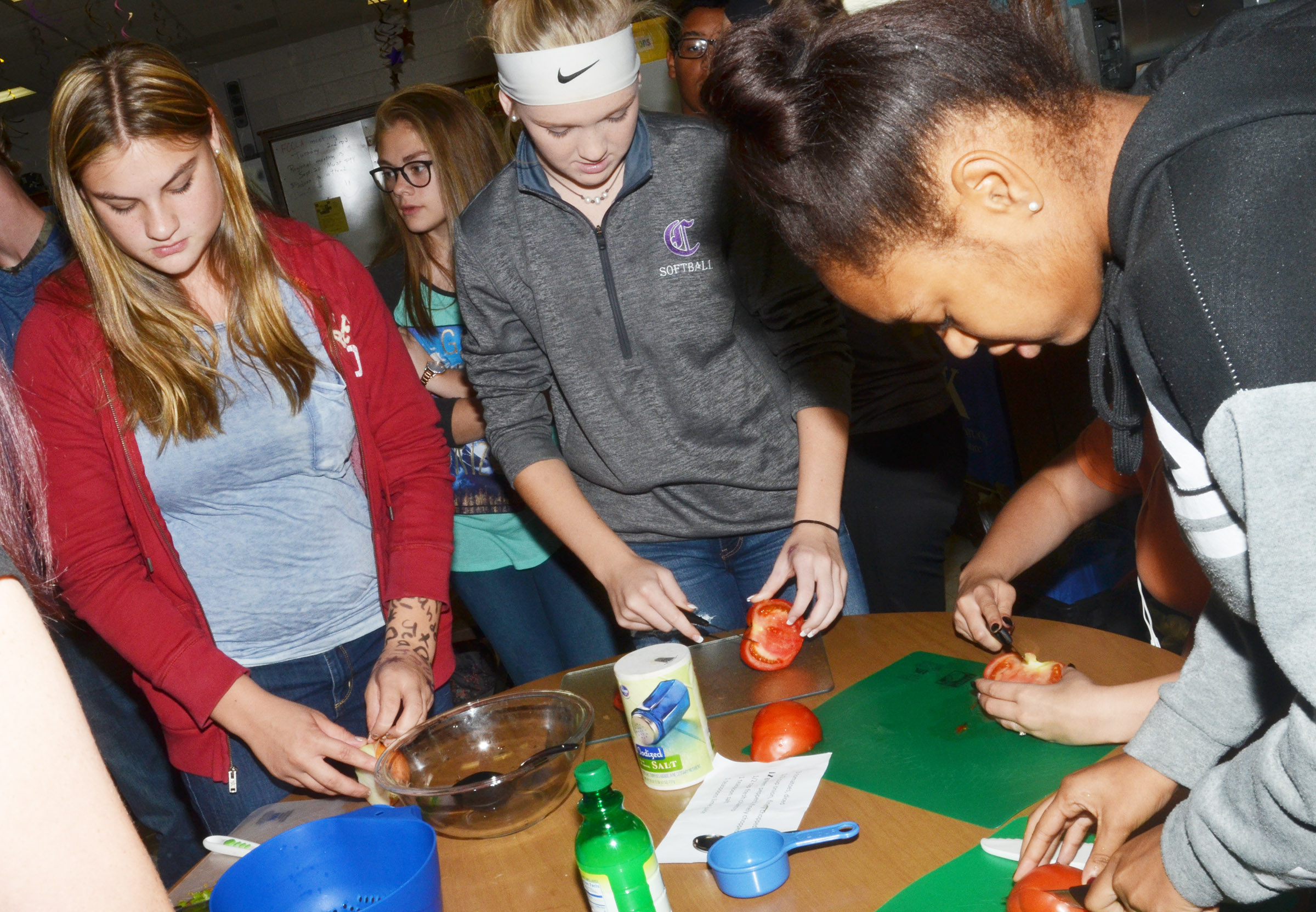From left, CHS freshmen Samantha Underwood and Catlyn Clausen and sophomore Isis Coleman chop vegetables.