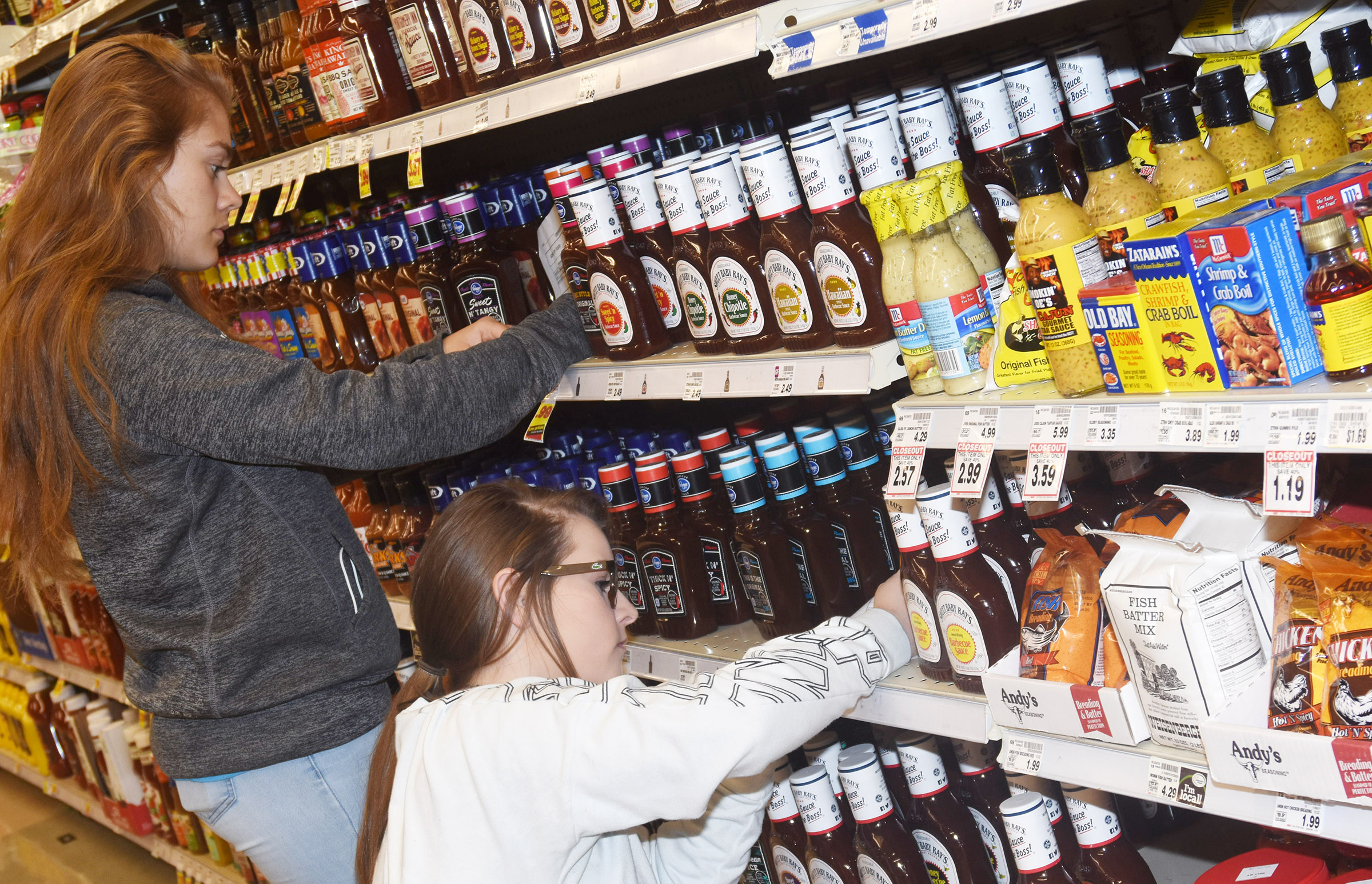 CHS freshmen Emily Kerns, at left, and Taylor Knight compare prices of barbecue sauce.