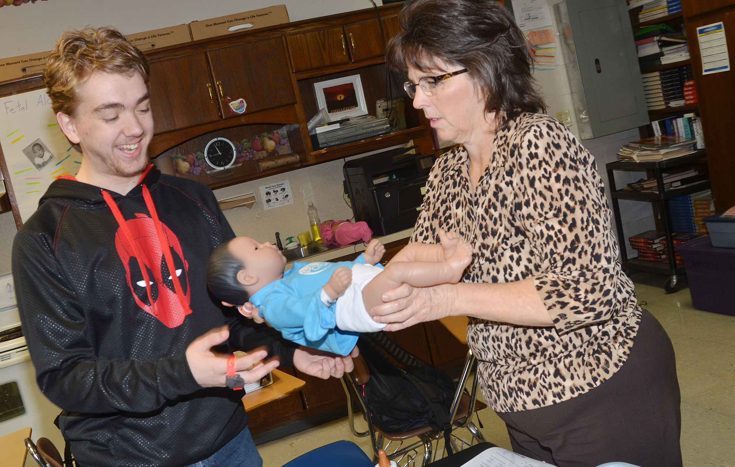 CHS teacher Deanna Campbell helps sophomore Anthony Shipione hold his Real Care baby.