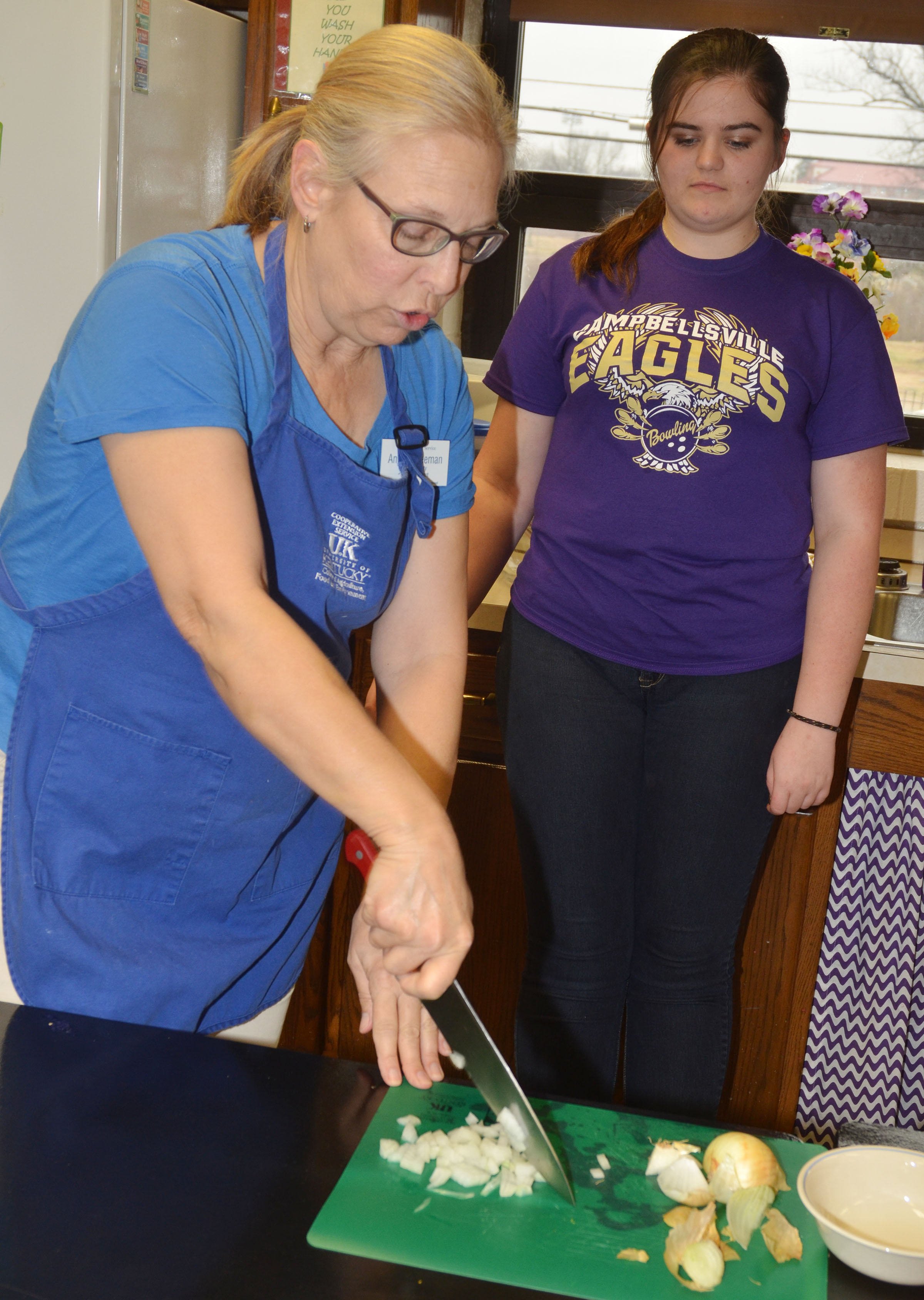 Angie Freeman, expanded foods and nutrition program assistant at Taylor County Extension Office, shows CHS junior Vivian Brown the proper way to chop onions.