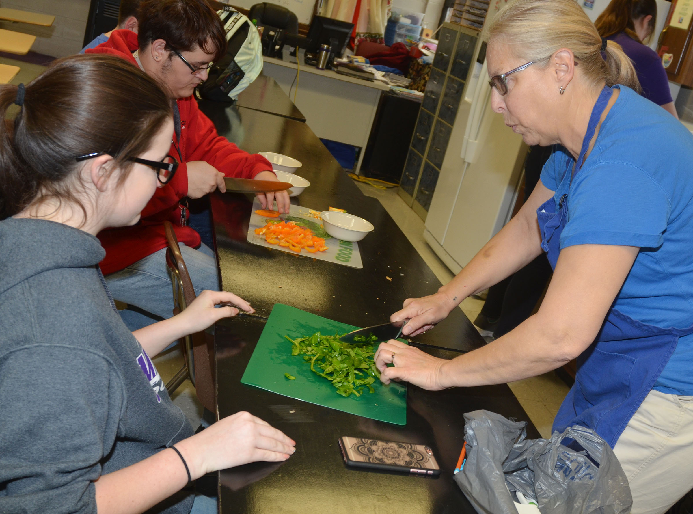 Angie Freeman, expanded foods and nutrition program assistant at Taylor County Extension Office, shows CHS freshman Sydney Wilson the proper way to cut spinach.