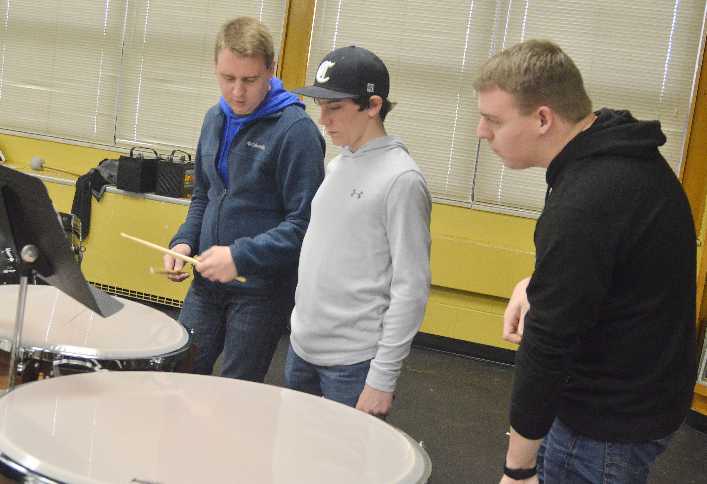 Lindsey Wilson College music students Taylor Cook, at left, and Tyler Cook, at right, help Campbellsville Middle School seventh-grader Peyton Dabney as he plays timpani.