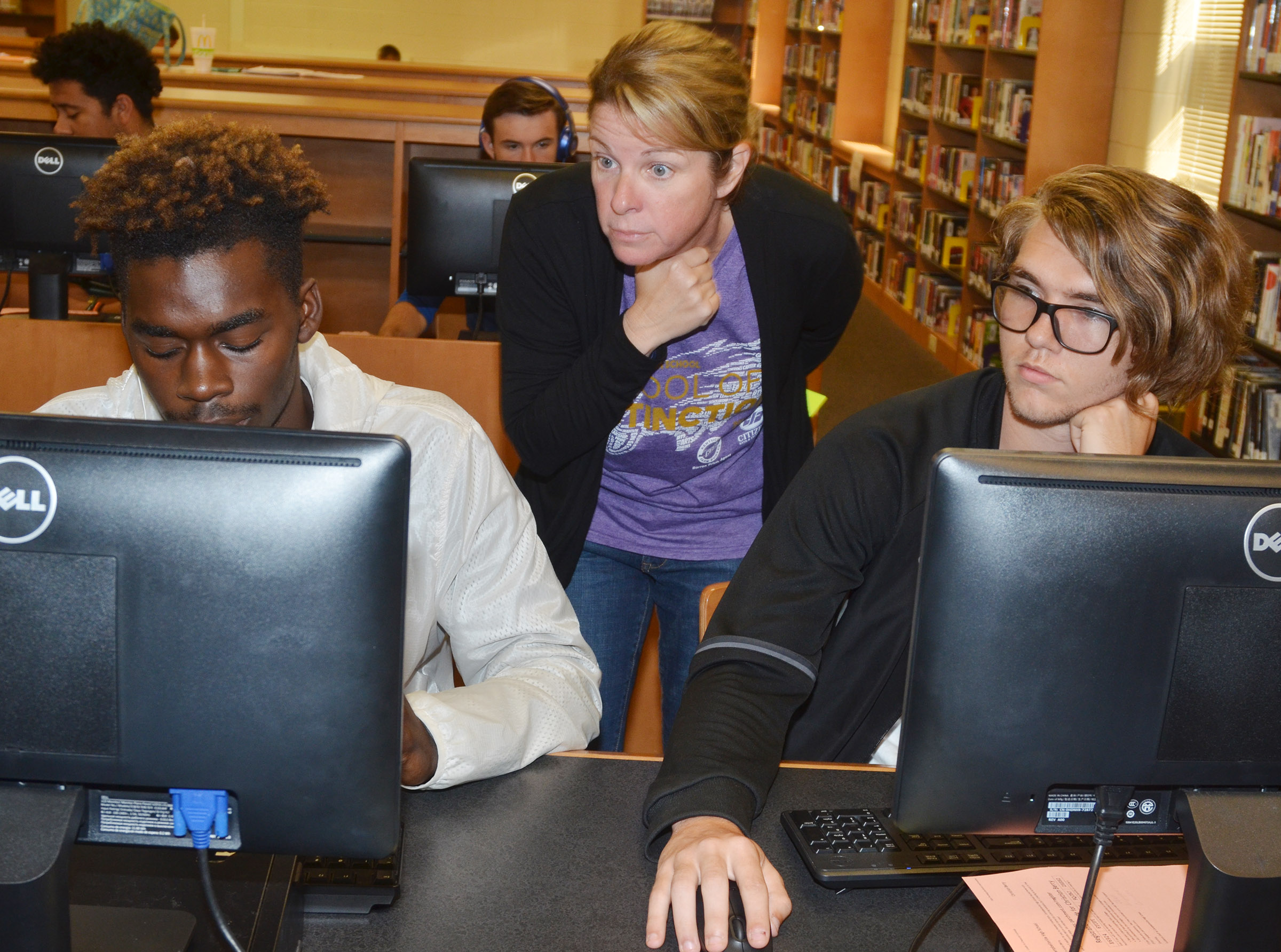 CHS College and Career Readiness Counselor Dee Doss helps seniors Jonta' Strawther, at left, and Christian Berry submit their college applications.