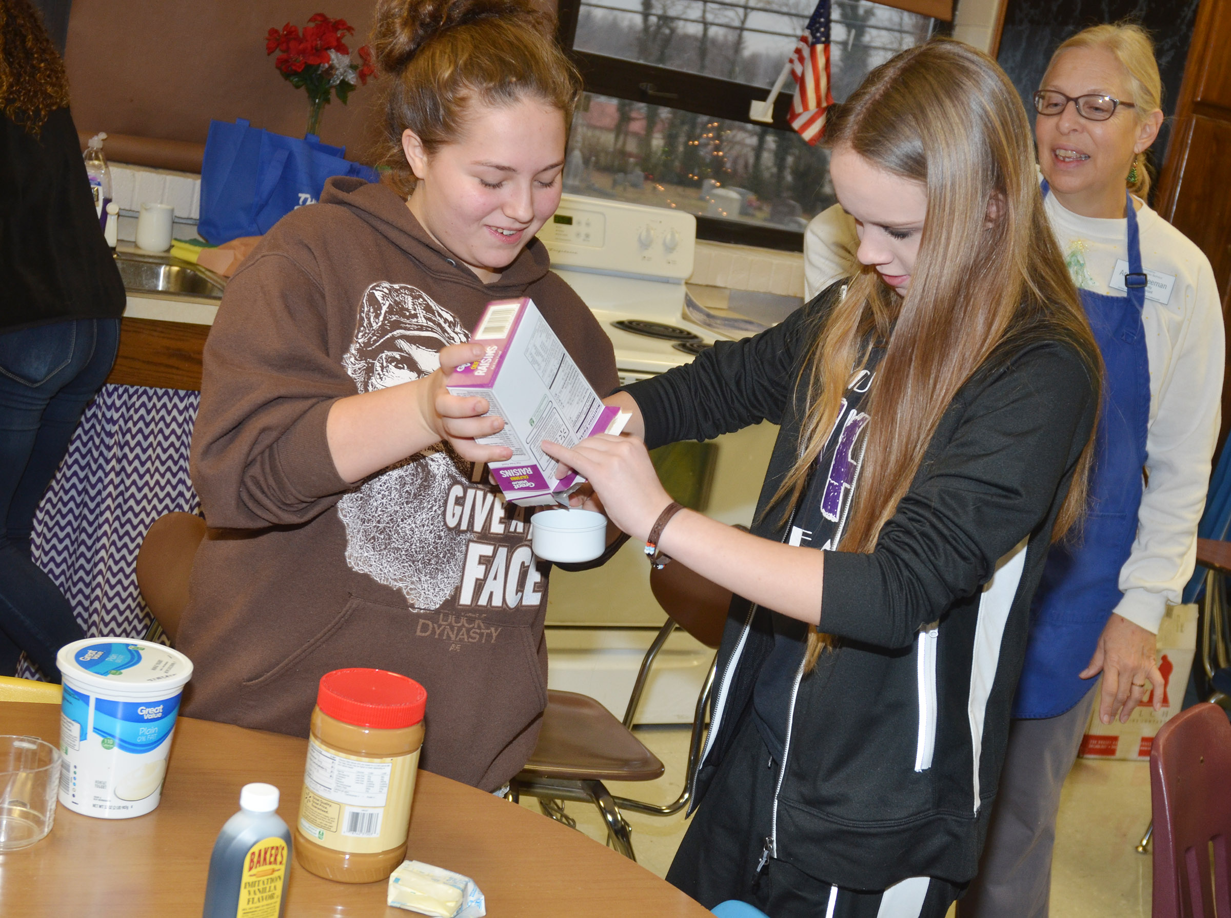 Angie Freeman, expanded foods and nutrition program assistant at Taylor County Extension Office, watches as CHS freshman Lilliana Hellard, at left, and Lisa Richter measure their ingredients.