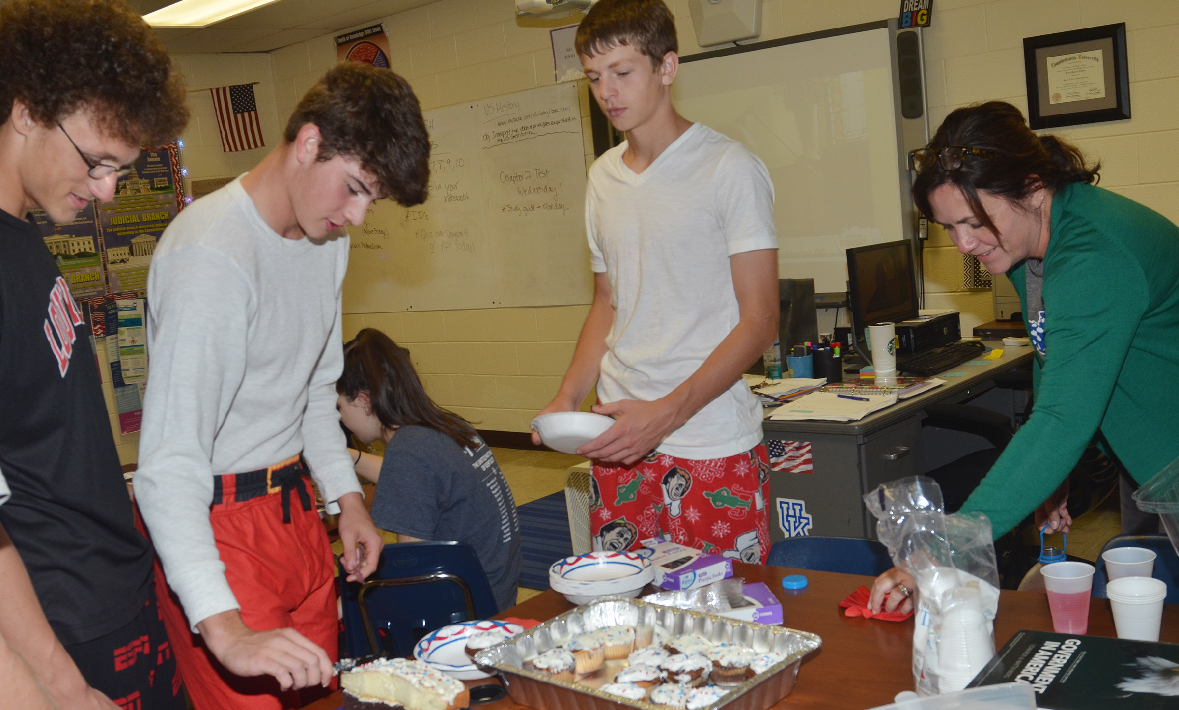 CES teacher Susan Dabney serves her students, from left, sophomores Brennon Wheeler, Mark Rigsby and Noah Hughes marble cake cupcakes and layer cake during their Constitution Day party.
