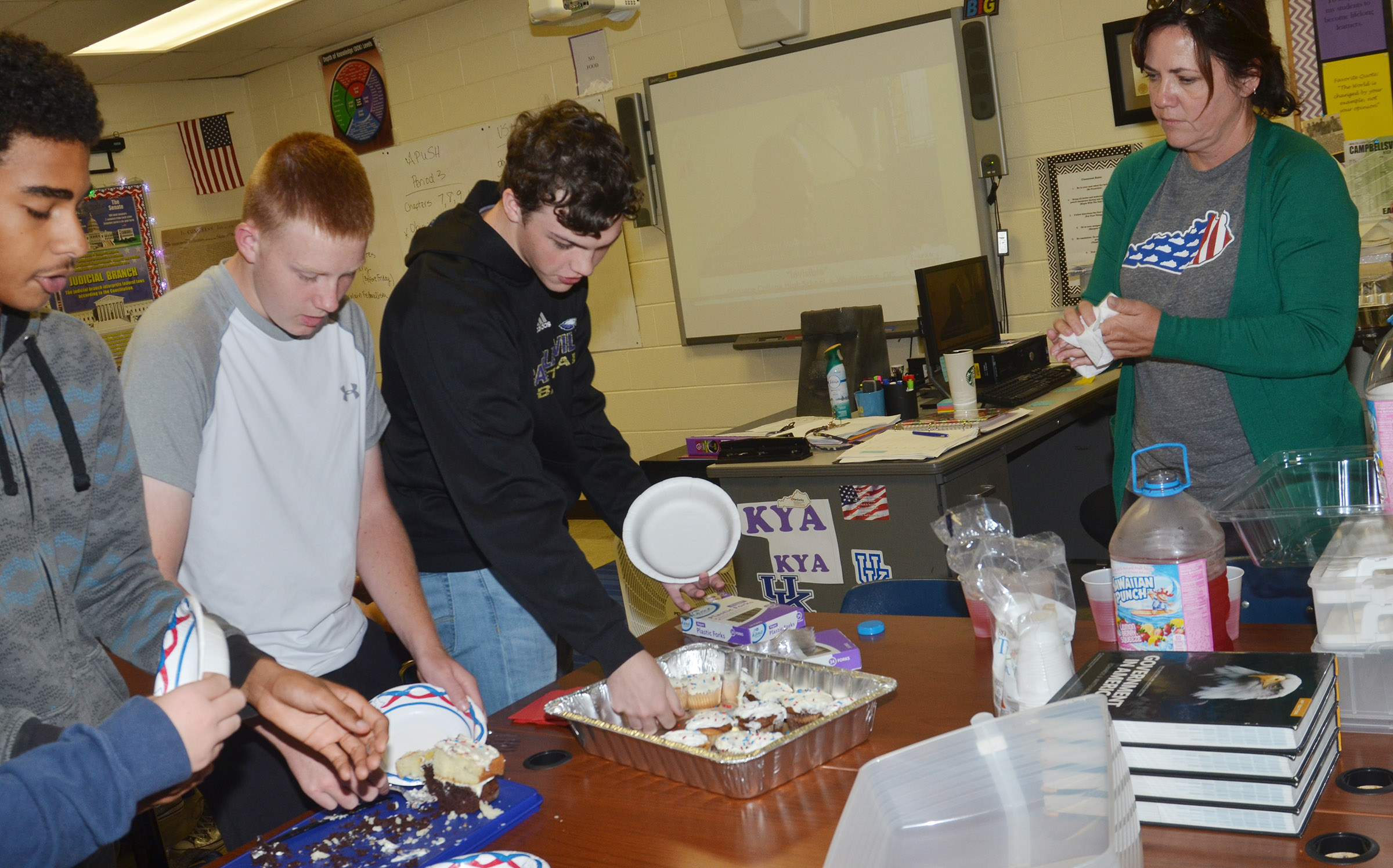 CES teacher Susan Dabney serves her students, from left, sophomores David Silva, Patrick Walker and Jimmy Russell marble cake cupcakes and layer cake during their Constitution Day party.