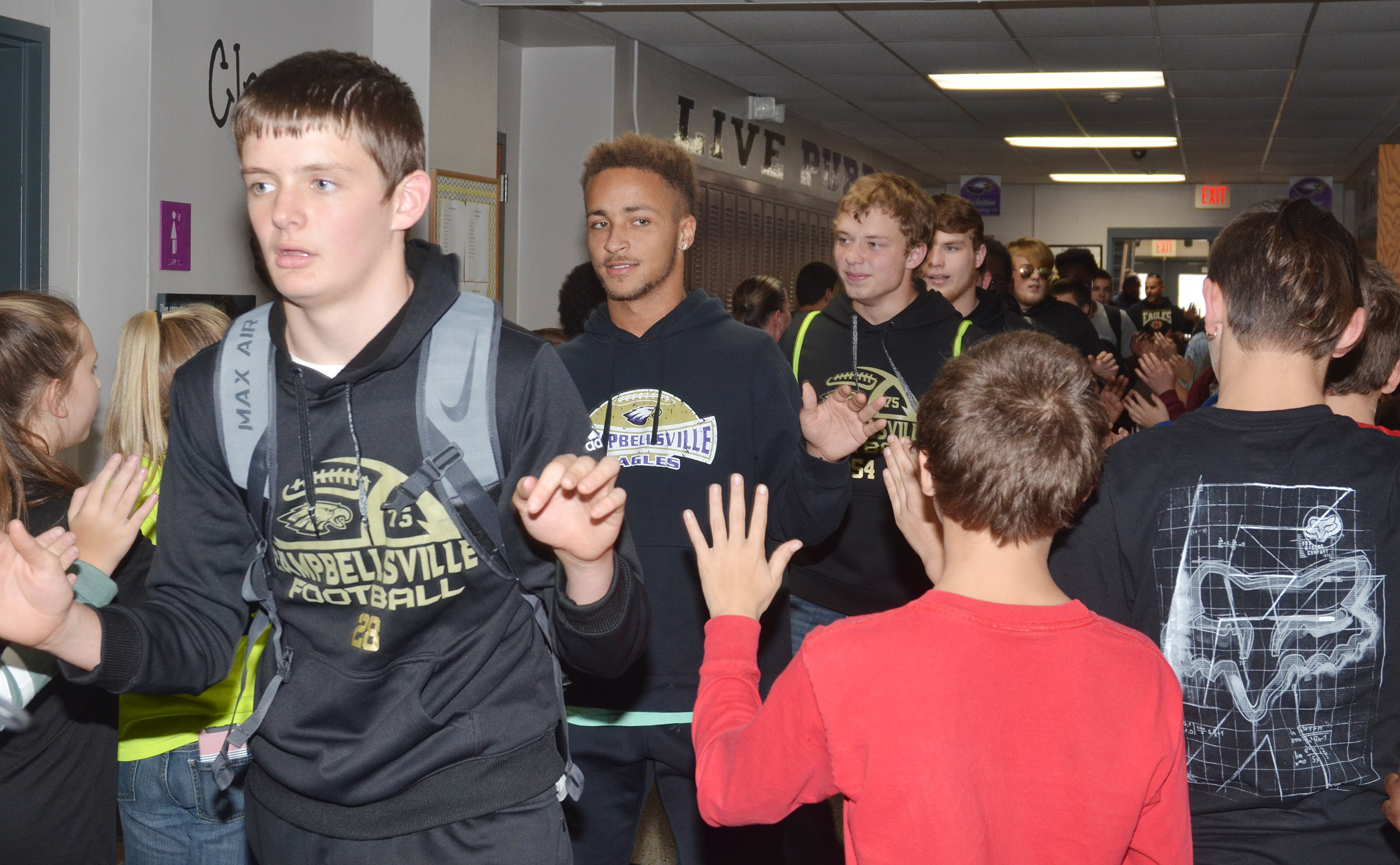 From left, CHS sophomore Blake Allen, senior Ethan Lay, sophomore Devon Reardon and junior Dakota Reardon walk with their teammates through CMS.
