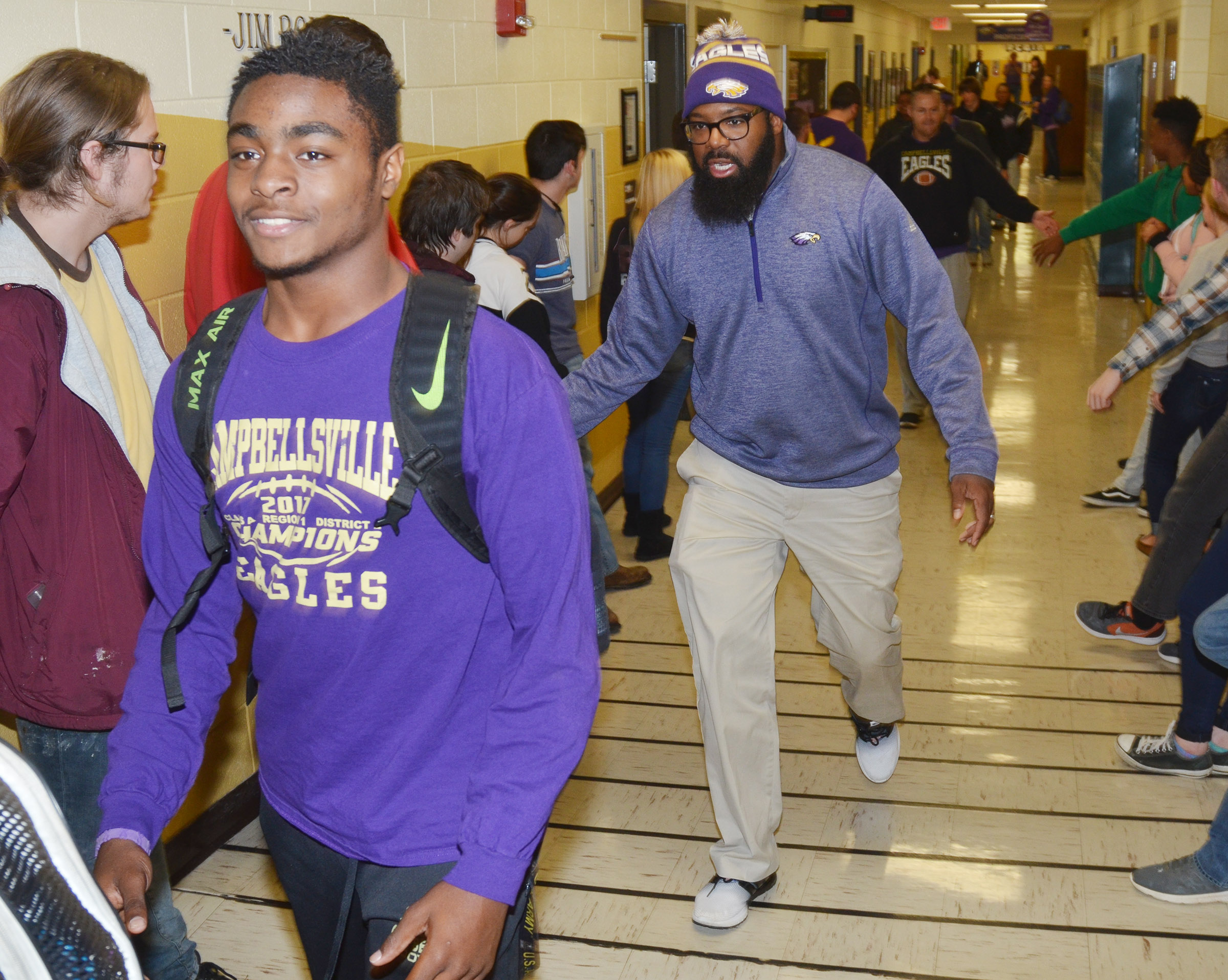 CHS junior Charlie Pettigrew and assistant coach Will Griffin walk through the CHS hallways.