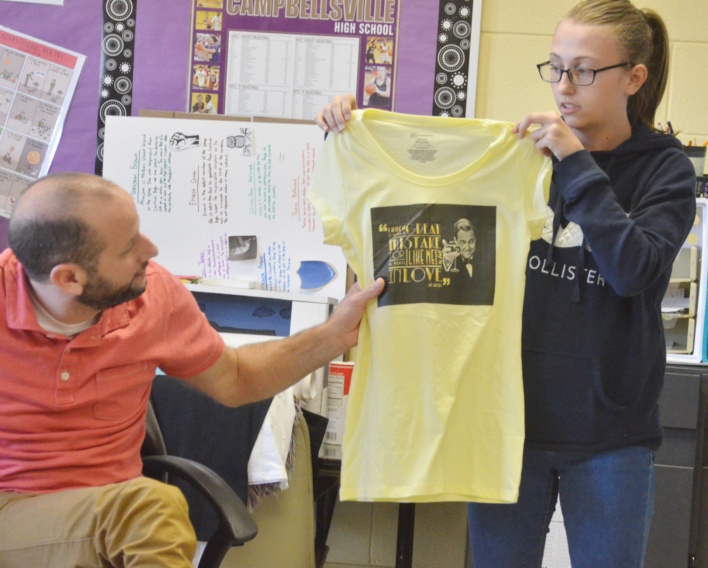 "CHS English teacher Ben Davis looks at the t-shirt that junior Brookelyn Franklin made based on the book ""The Great Gatsby."""
