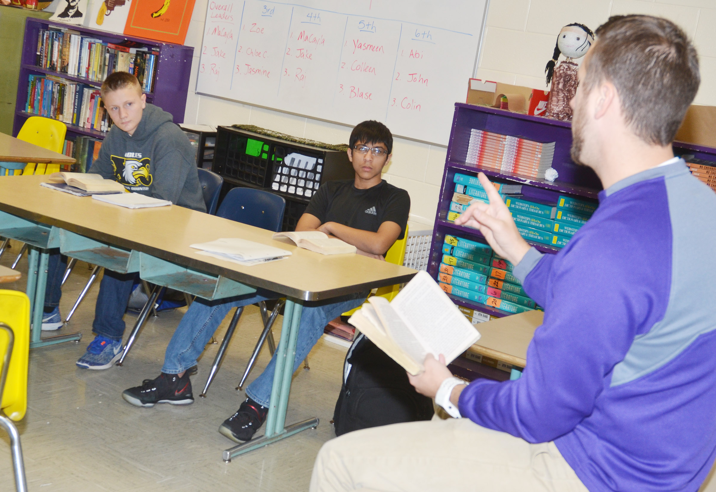 "CHS teacher Tyler Hardy talks to his students about the plot of ""To Kill A Mockingbird."" Pictured are CHS freshmen Jake Dicken, at left, and Raj Patel."