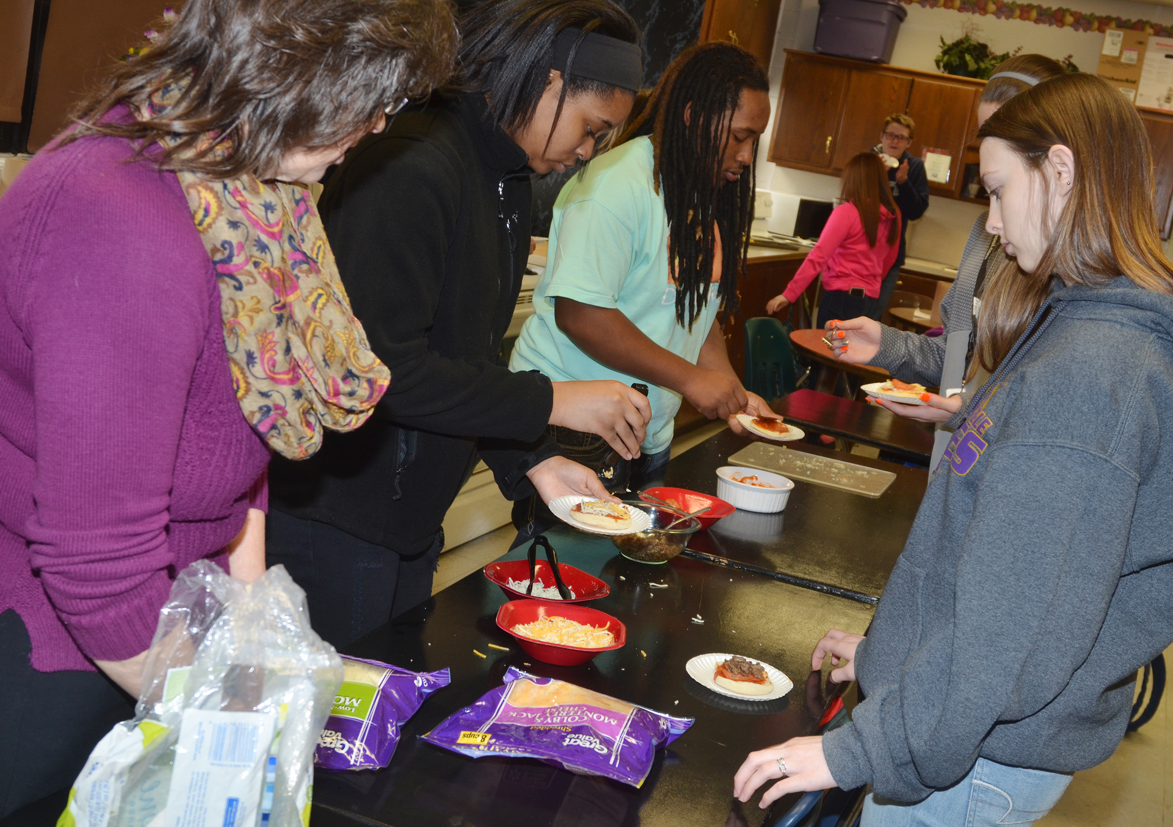 CHS teacher Deanna Campbell, at left, helps students, from left, junior Vonnea Smith and sophomores Ceondre Barnett and Caleigh Bright make English muffin pizzas.