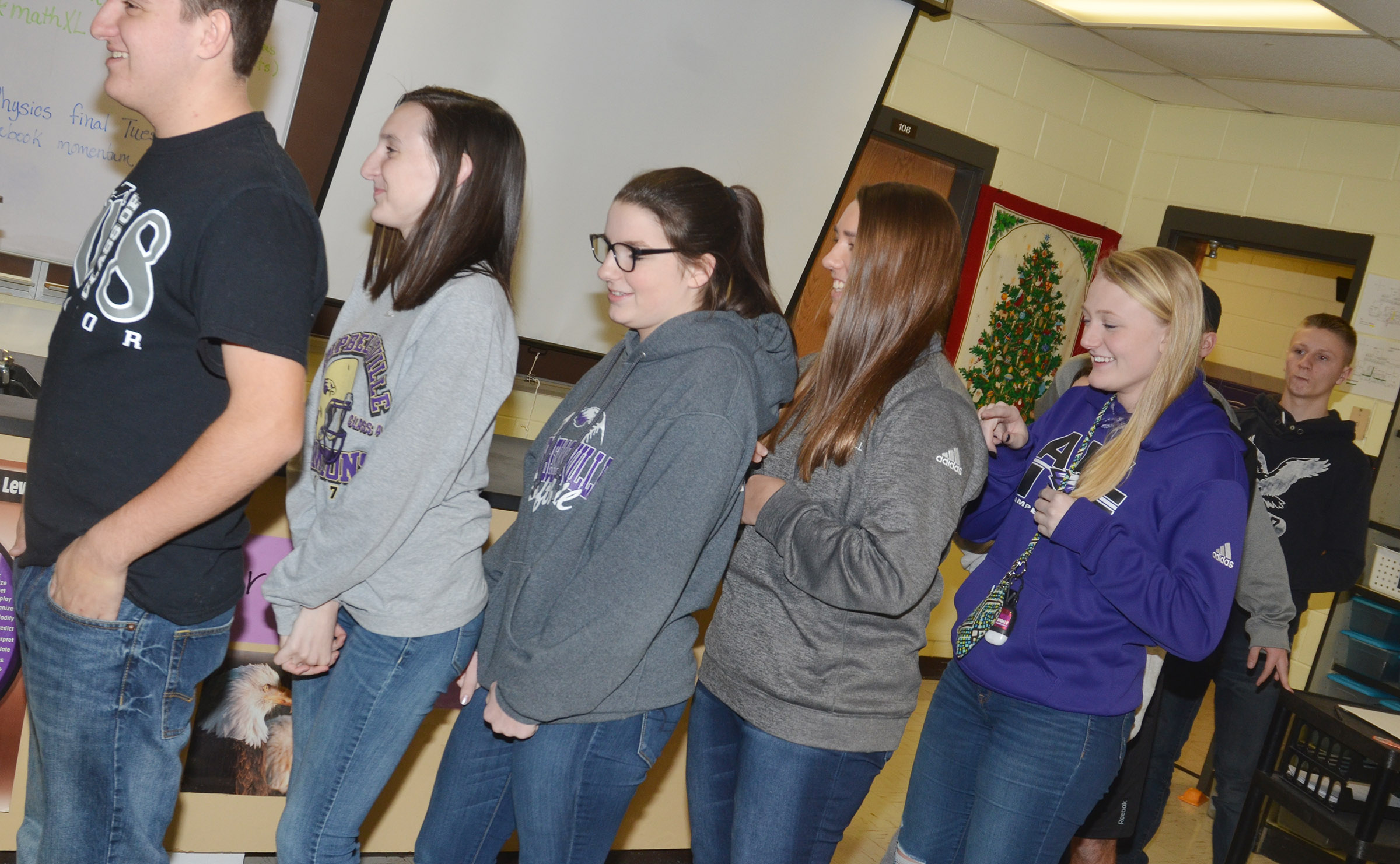 "CHS FCA members play an icebreaker game in which students form a line and ""write"" a symbol on each other's backs. The person at the front of the line tries to guess the symbol. Above, CHS junior Abbie Dicken writes on freshman Abi Wiedewitsch's back."