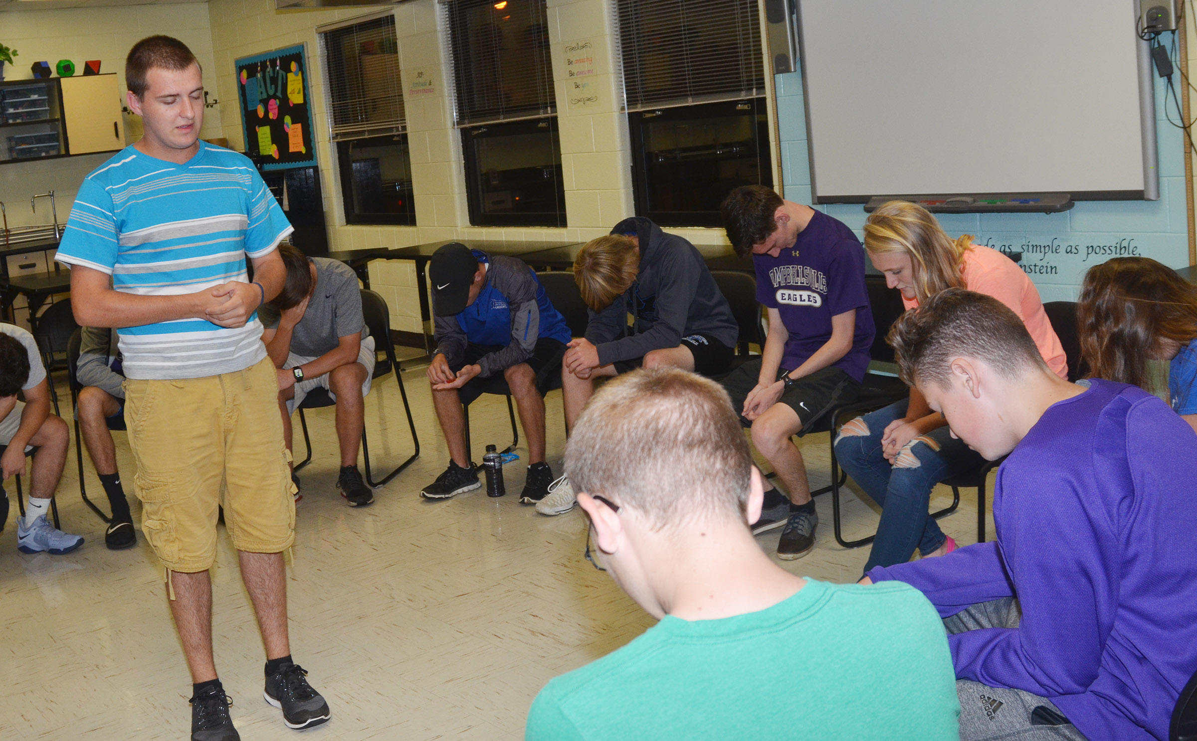 CHS senior Austin Fitzgerald prays with his fellow FCA members.